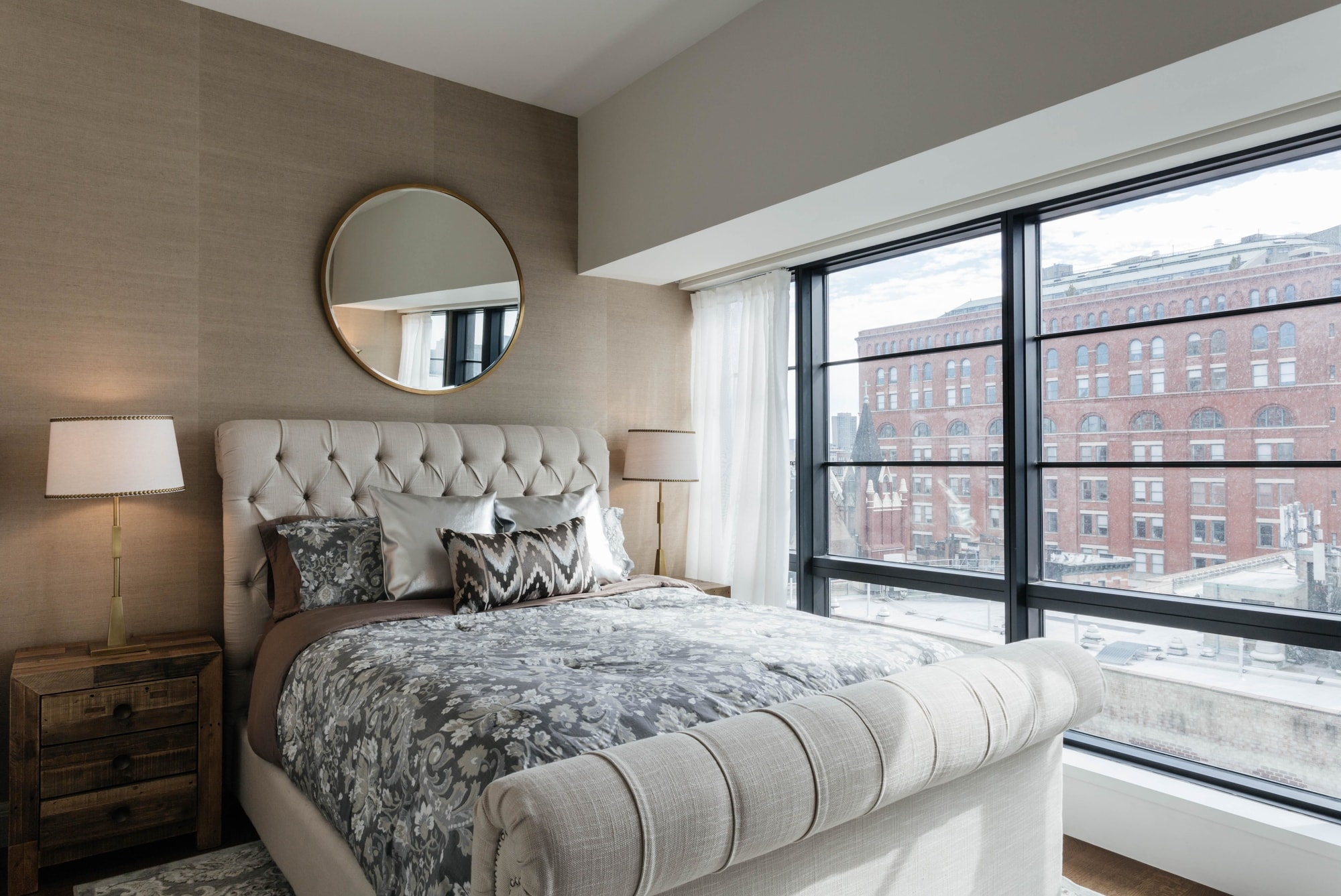 Bedroom with circular mirror hanging above bed