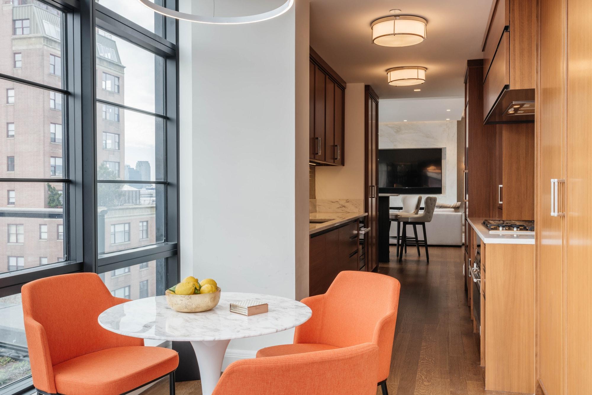 Bright breakfast nook with orange chairs