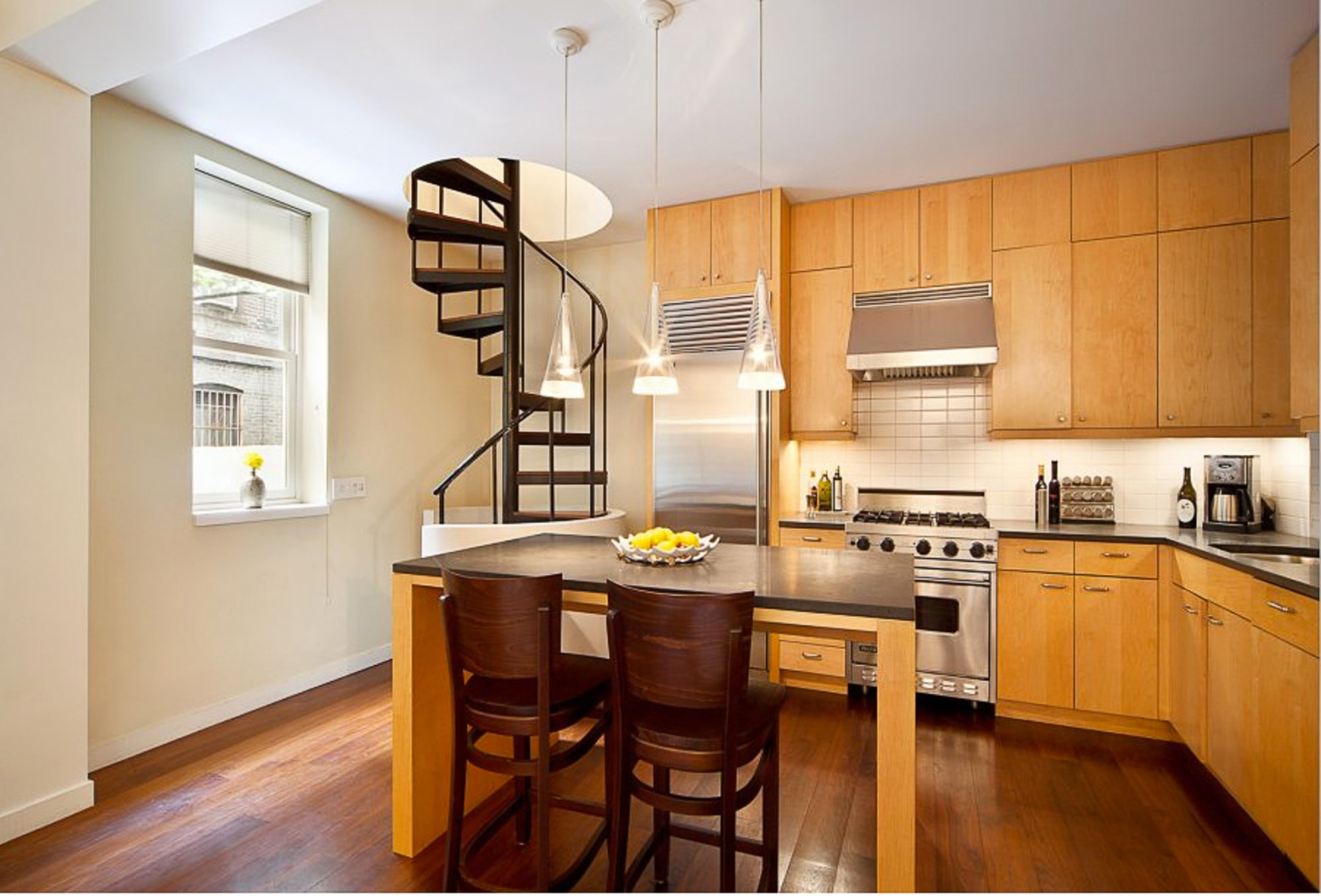 Modern kitchen with spiral staircase leading through the ceiling