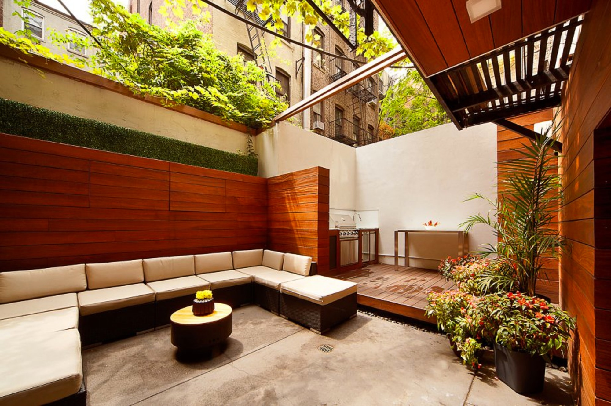 Outdoor seating area with wood panels and potted plants