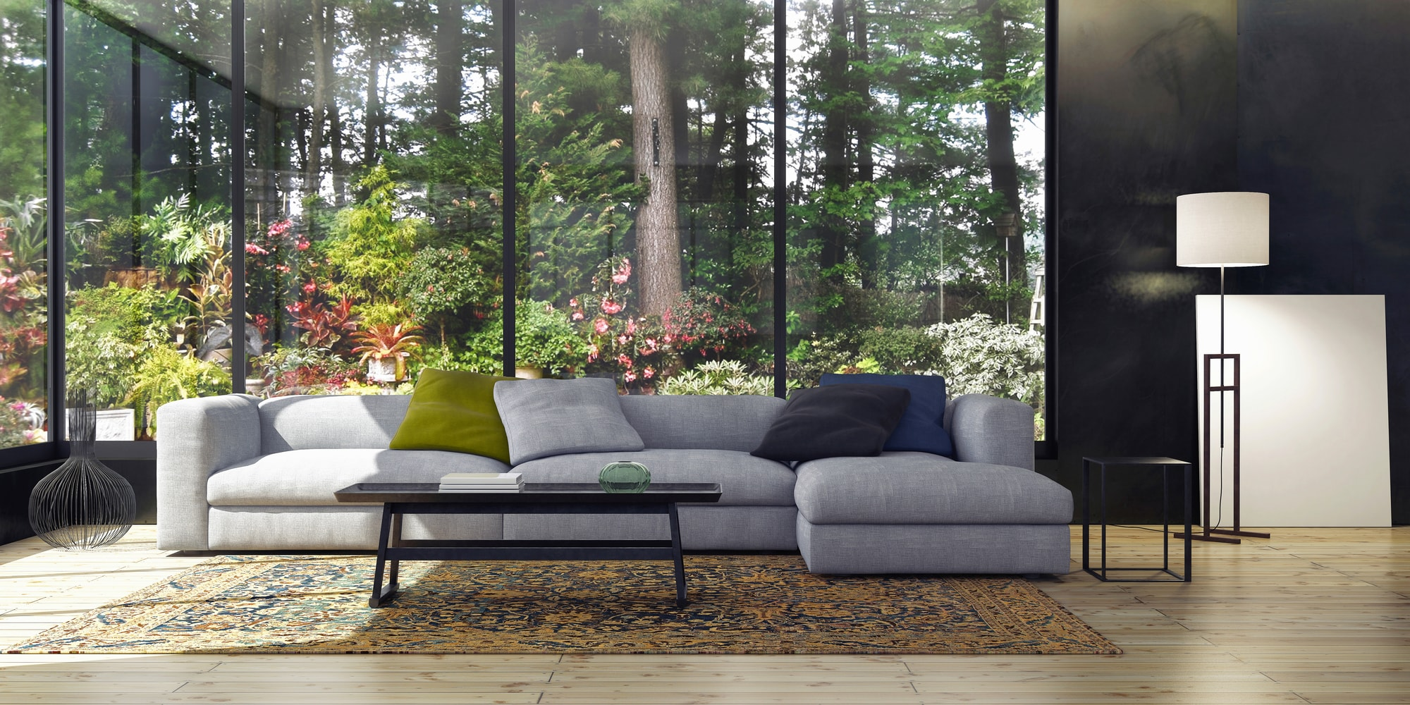 Large grey sectional sofa in front of glass windowed garden