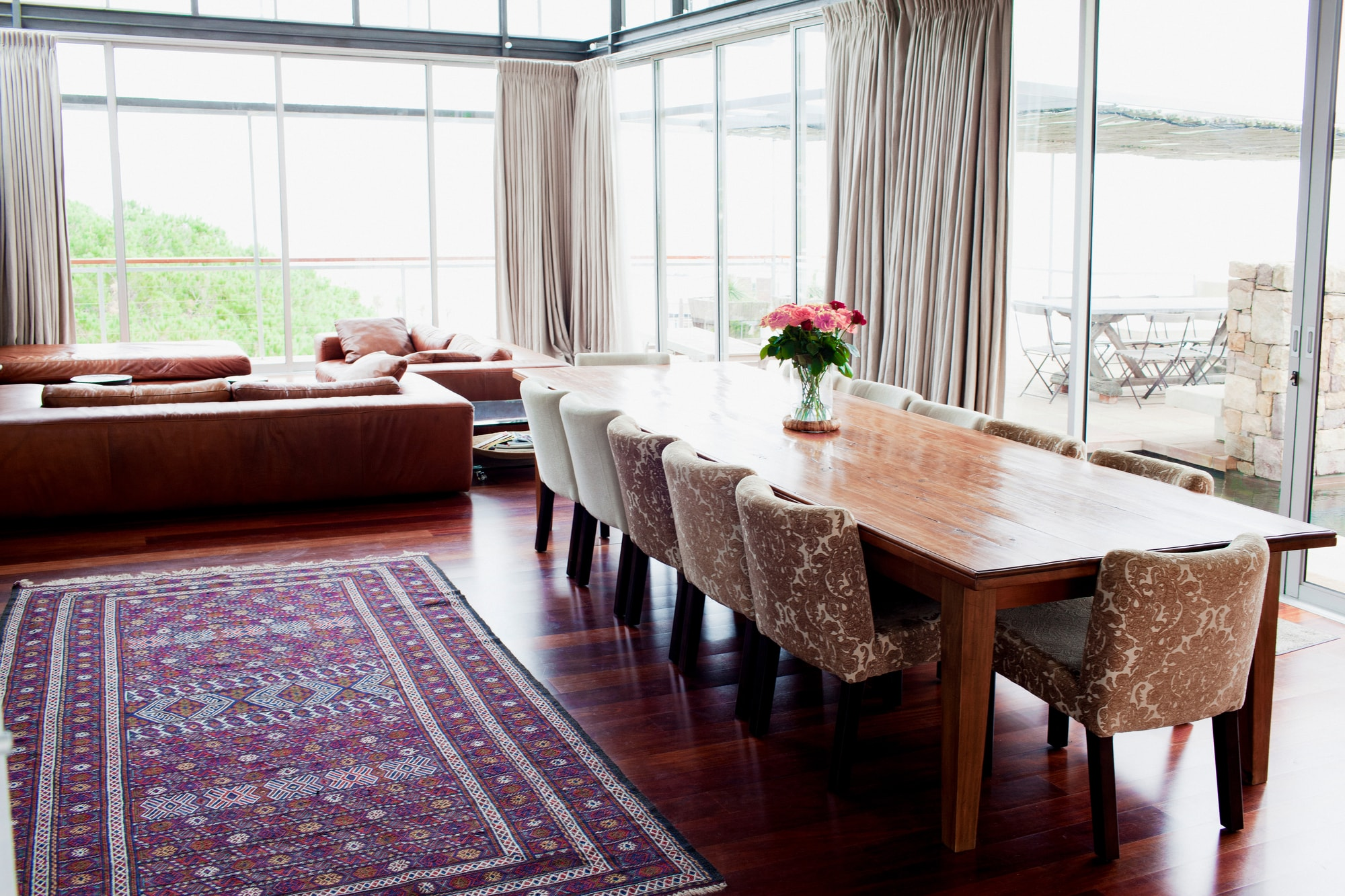 Long wooden dining room table and leather sofas