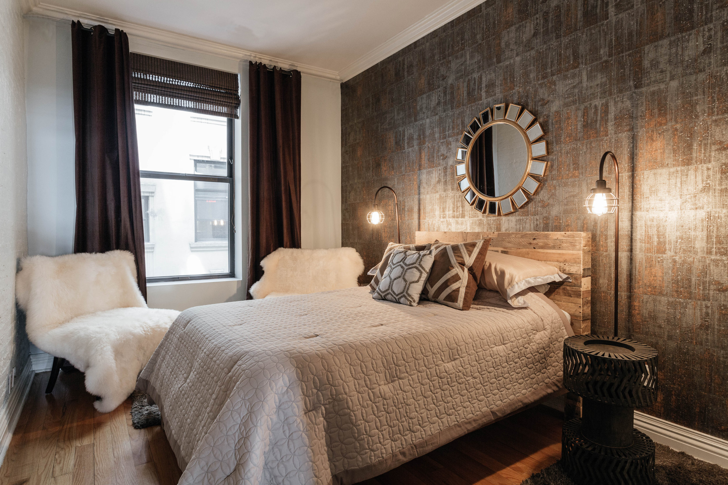 Bedroom with dark textured wall and standing bare bulb lamps
