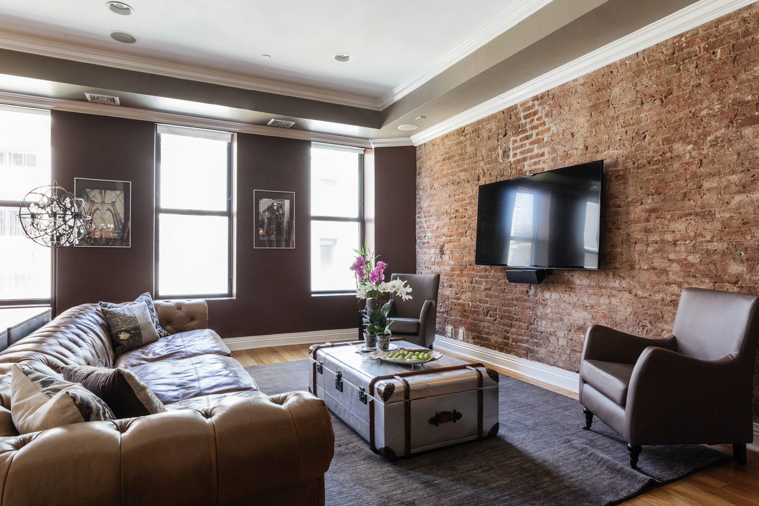 Modern living room with brown leather sofa and tv mounted on exposed brick wall