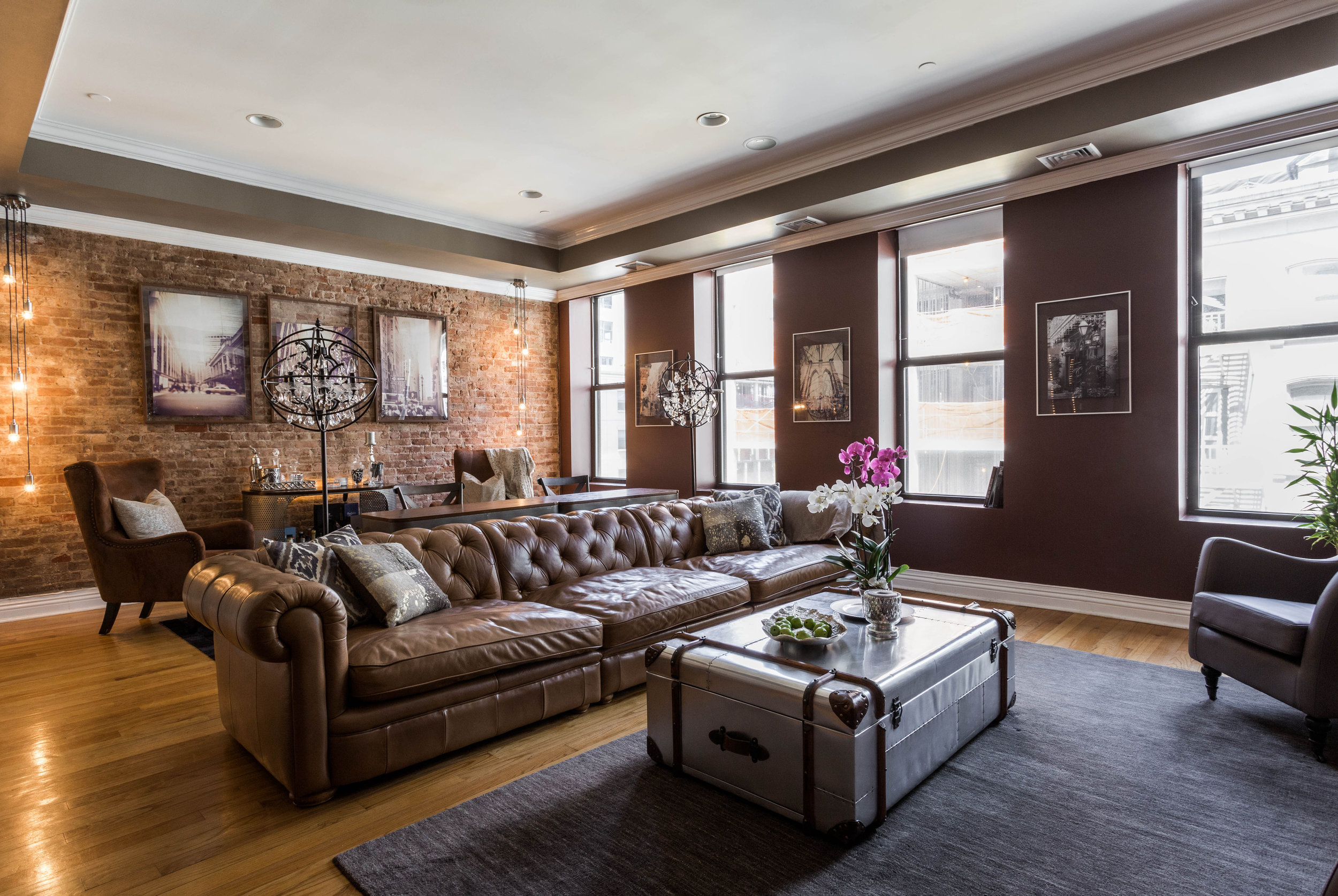 Tribeca industrial living room with custom chesterfield sofa and restoration hardware coffee table