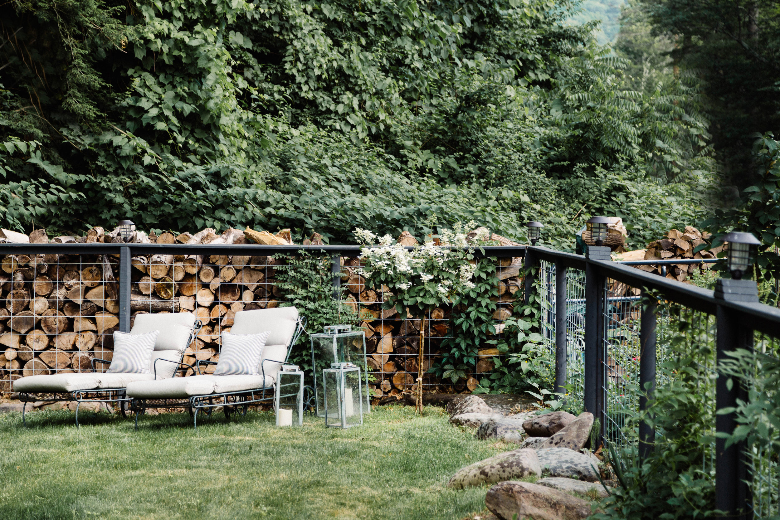 Outdoor area with lounge chairs and stacked wood
