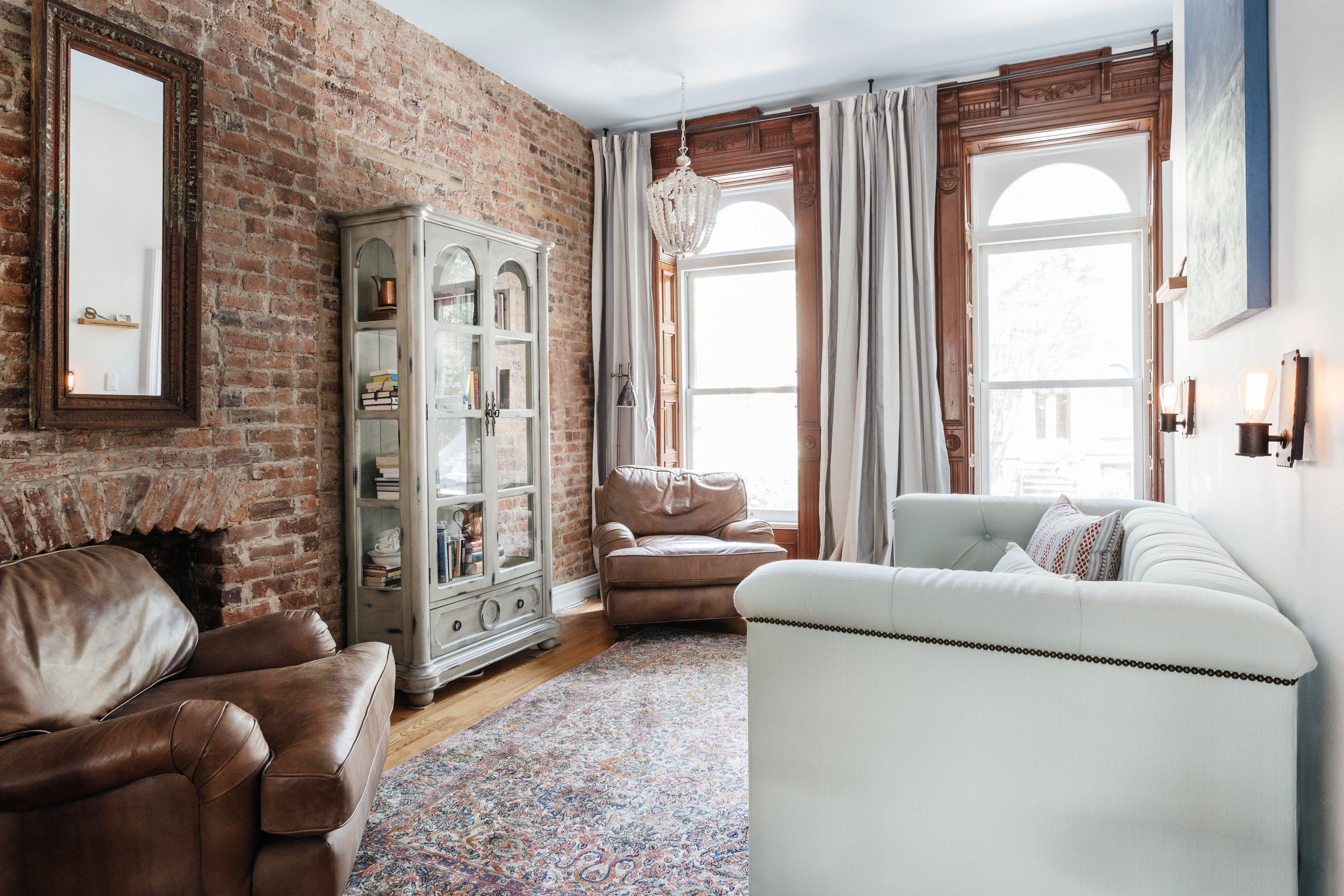 Bright living room space with luxurious brown leather chairs and original wooden casement windows