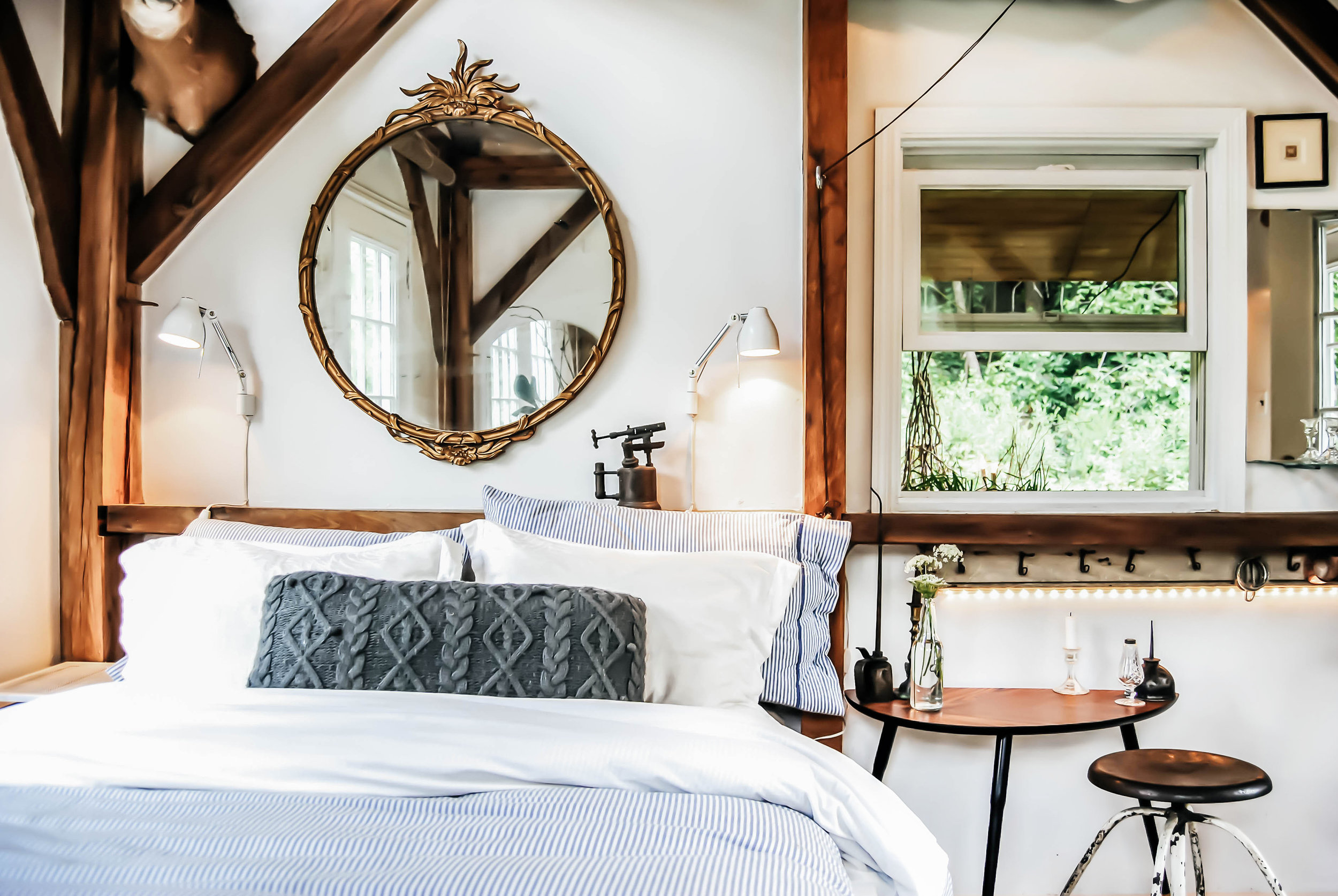 Bed area in tiny house with ornate metal mirror hanging over bed