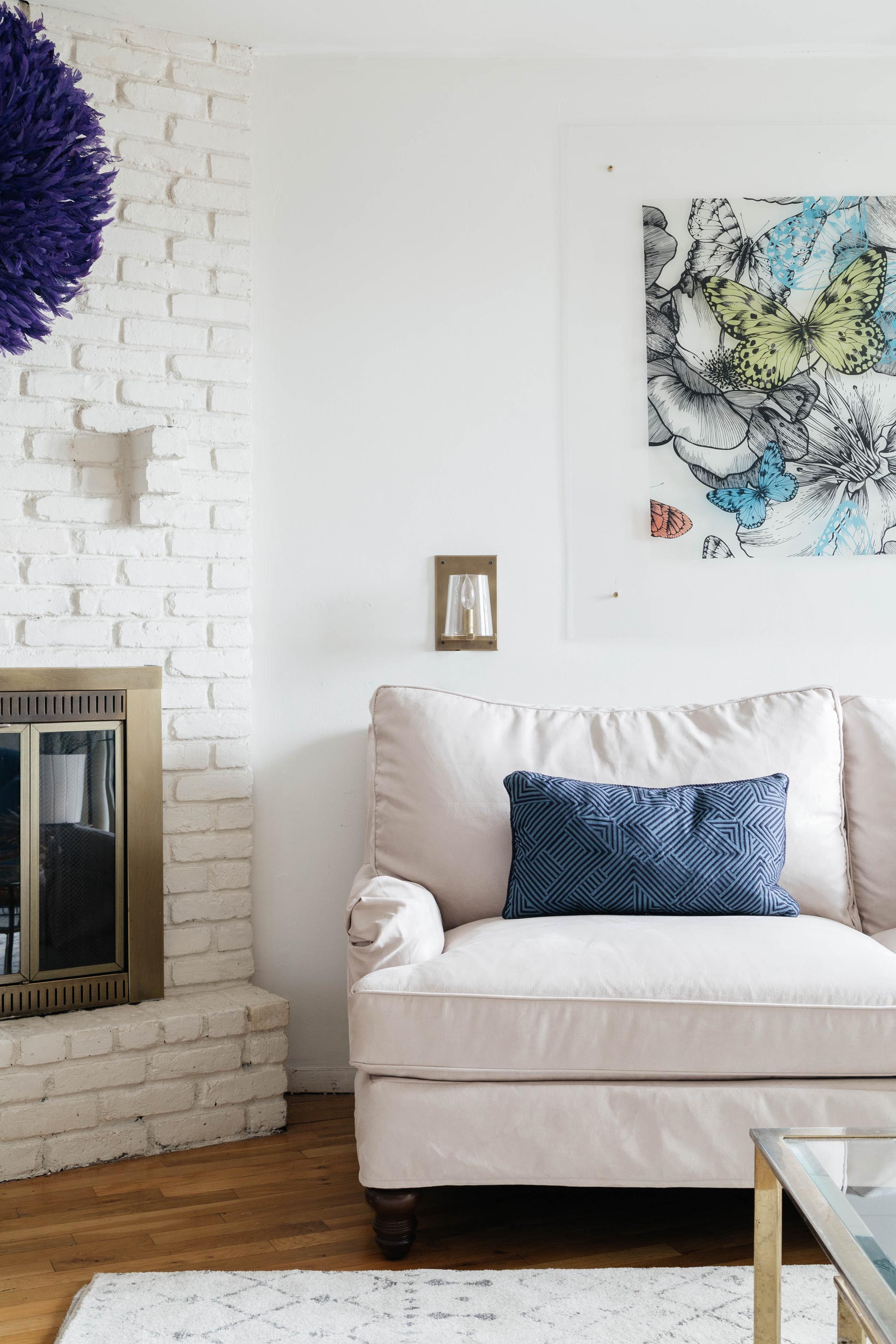 Corner of living room space with white painted fireplace
