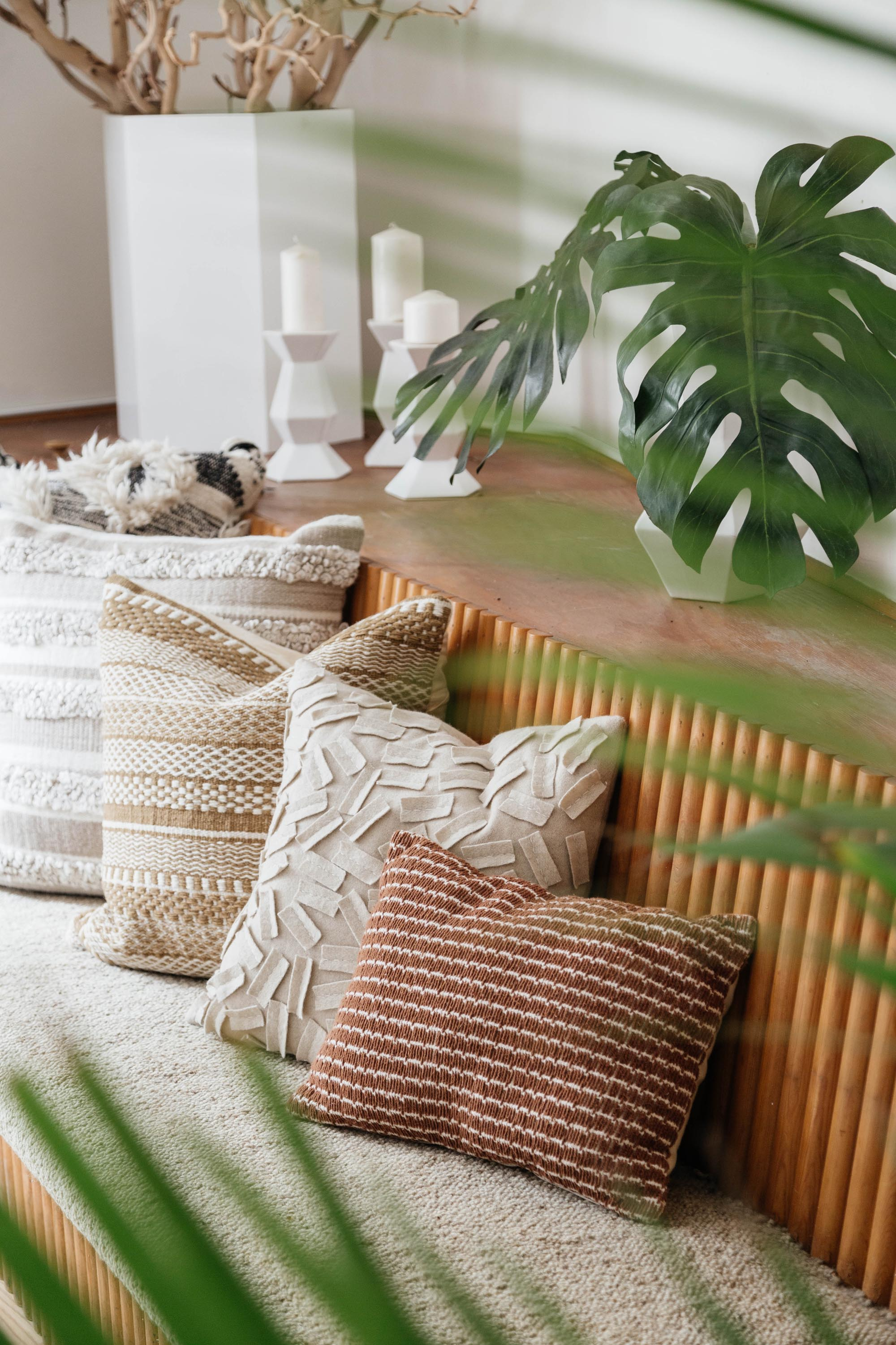 Custom built wooden sectional bench with throw pillows and plants