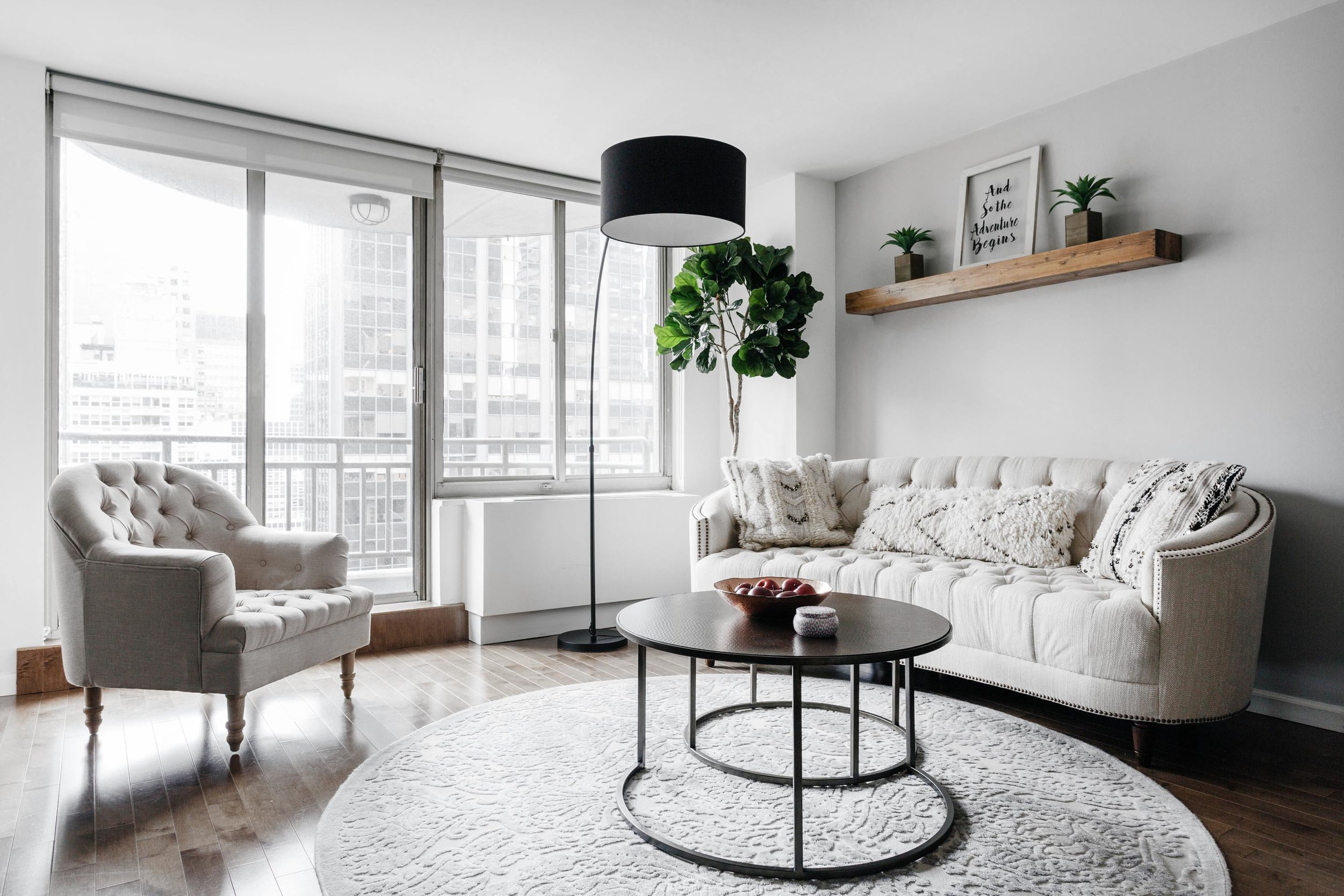 Bright living room with soft white sofas and wooden shelf on wall