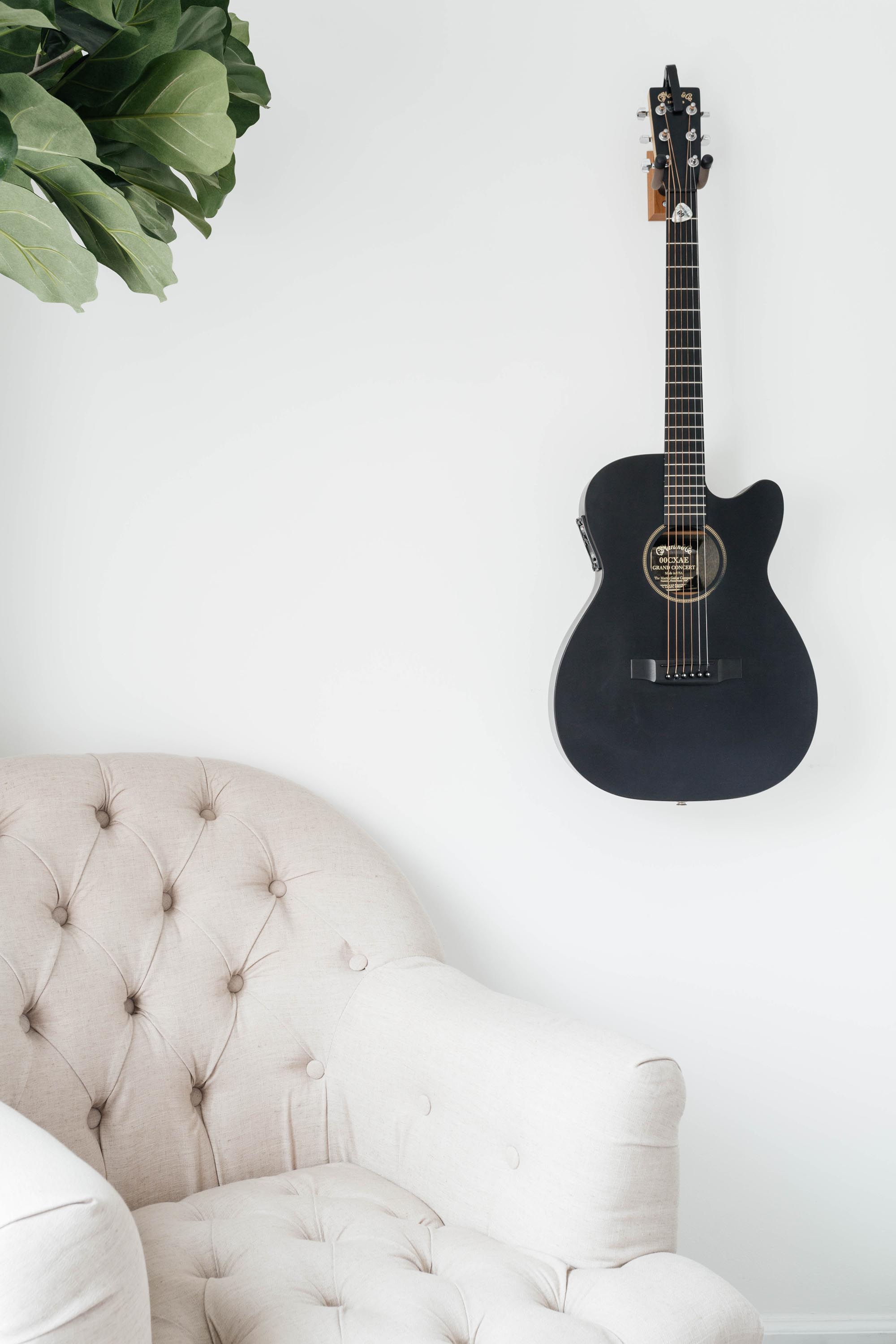 Soft white sofa with dark blue guitar hanging on wall