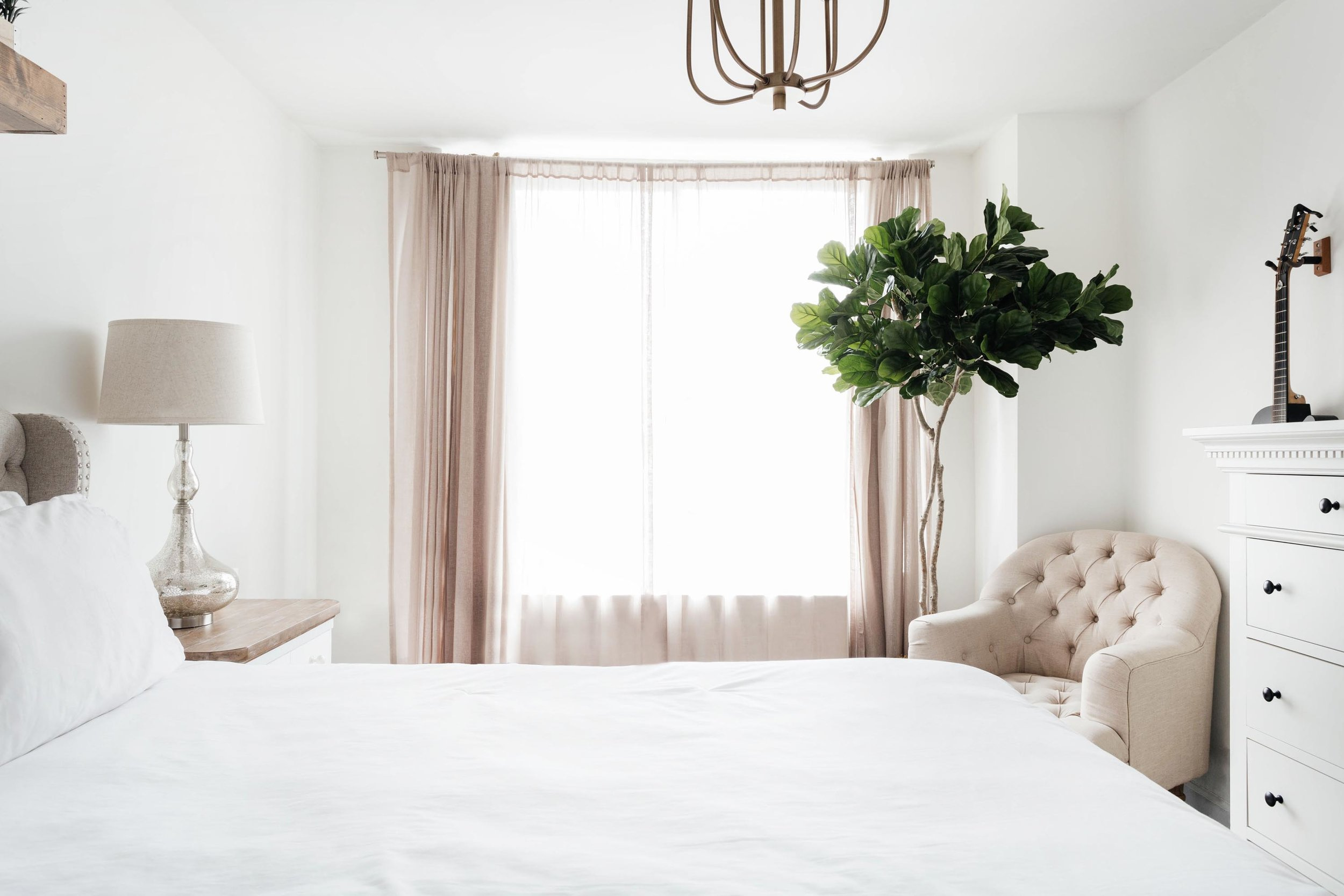 Bright bed room with soft white colors and green plant