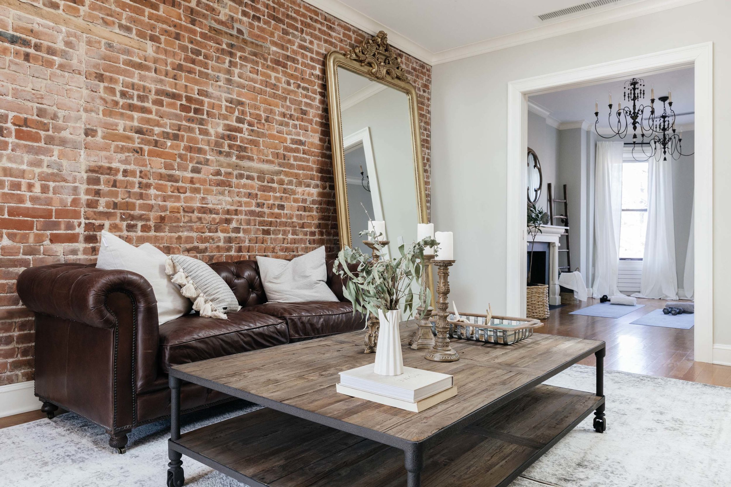 Sitting area with dark brown plush leather sofa and exposed brick wall