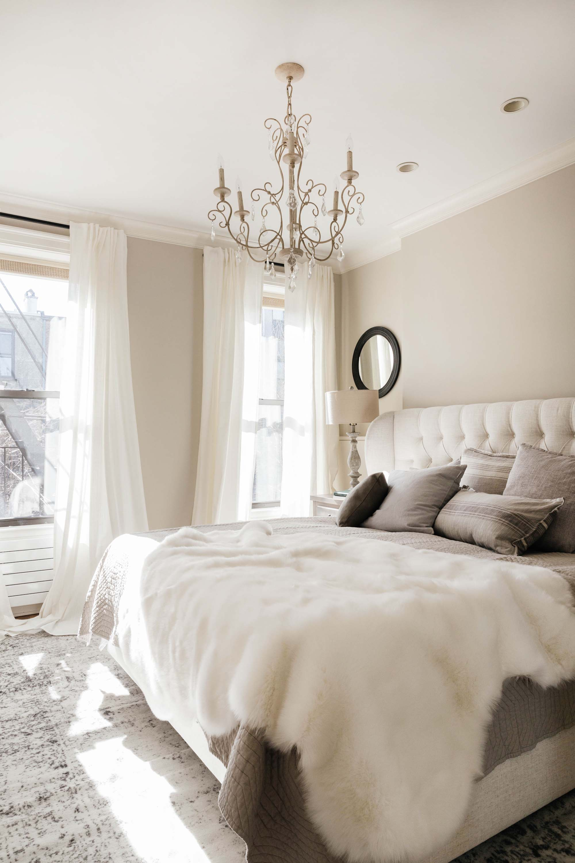 Bright bedroom with sheepskin draped over the bed