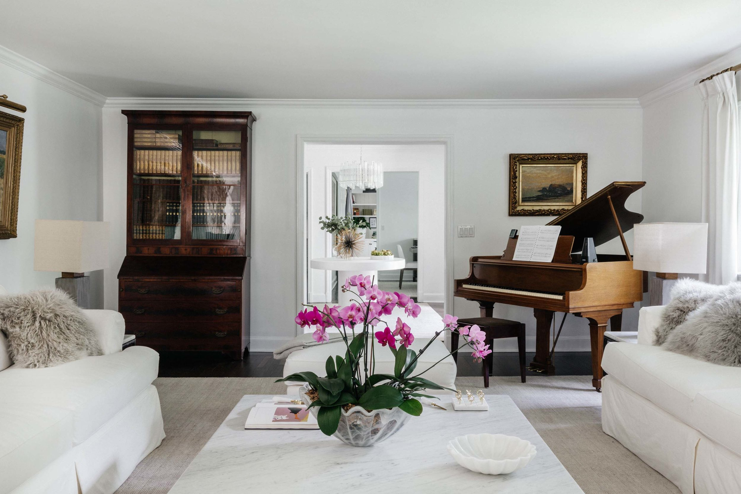 Living room with white painted walls, white sofa, center table and grand piano