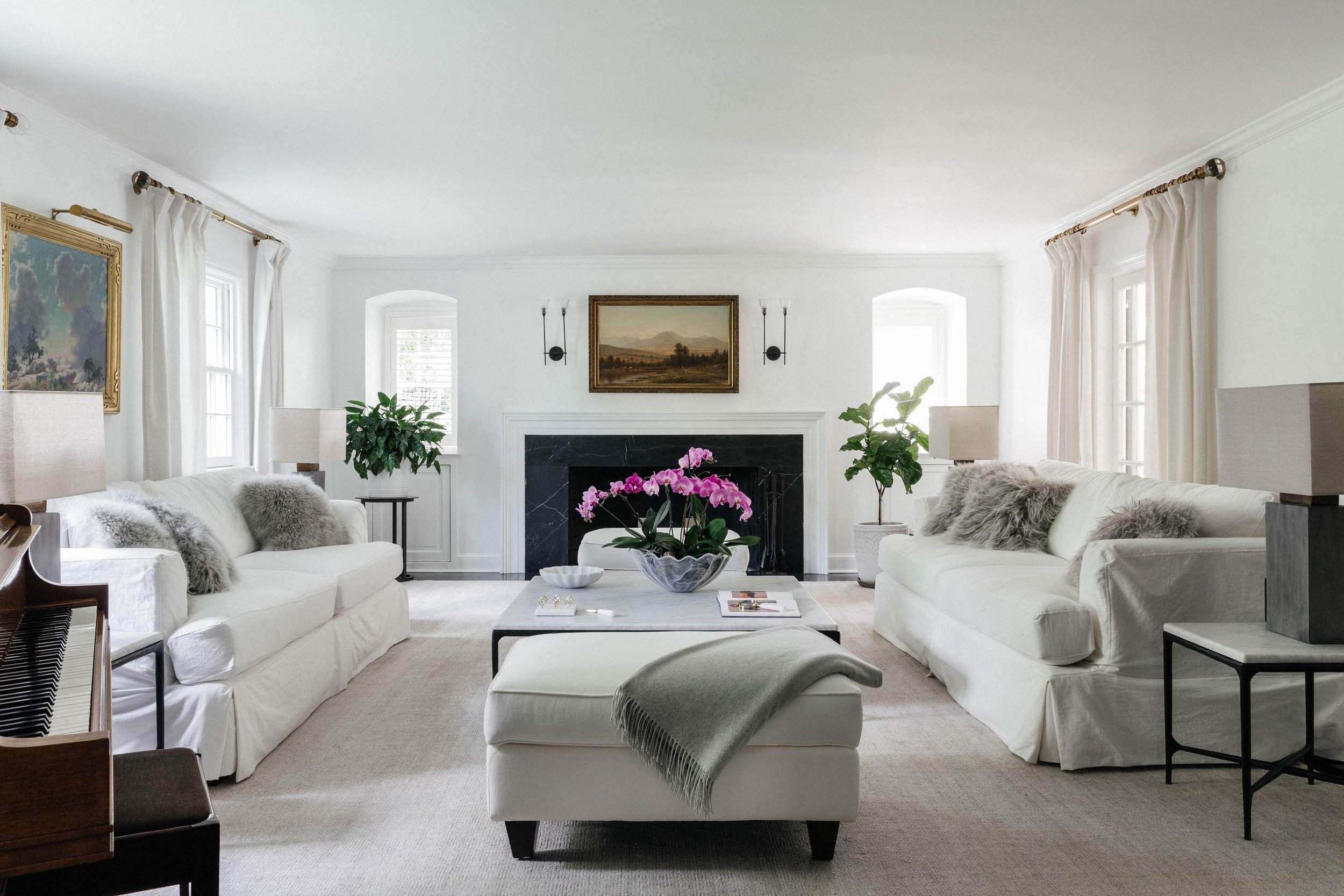 Living room with fireplace, white painted walls, white sofa, center table and ottoman