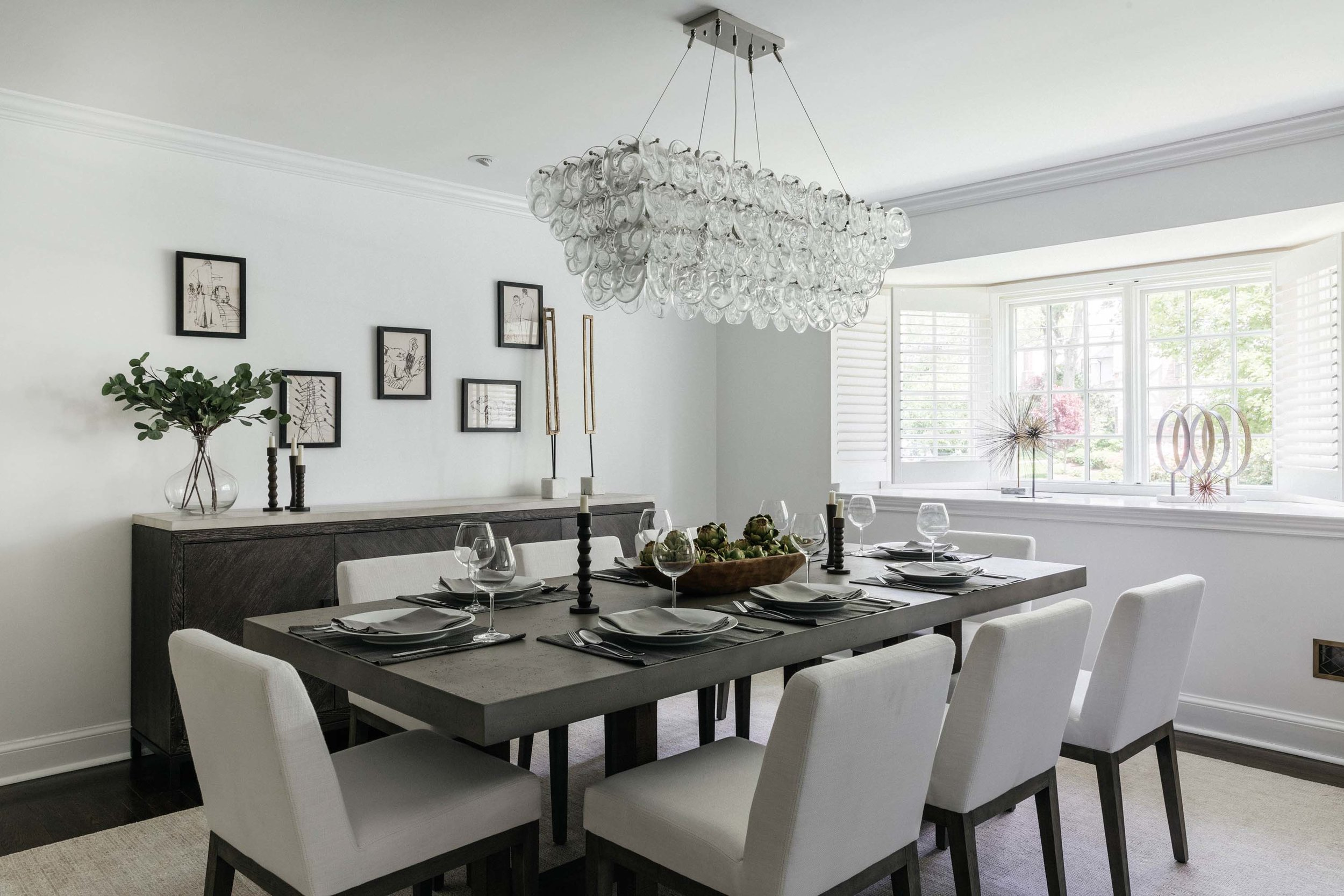 Dining room with dining table, plates, wine glasses, white painted walls and modern chandelier
