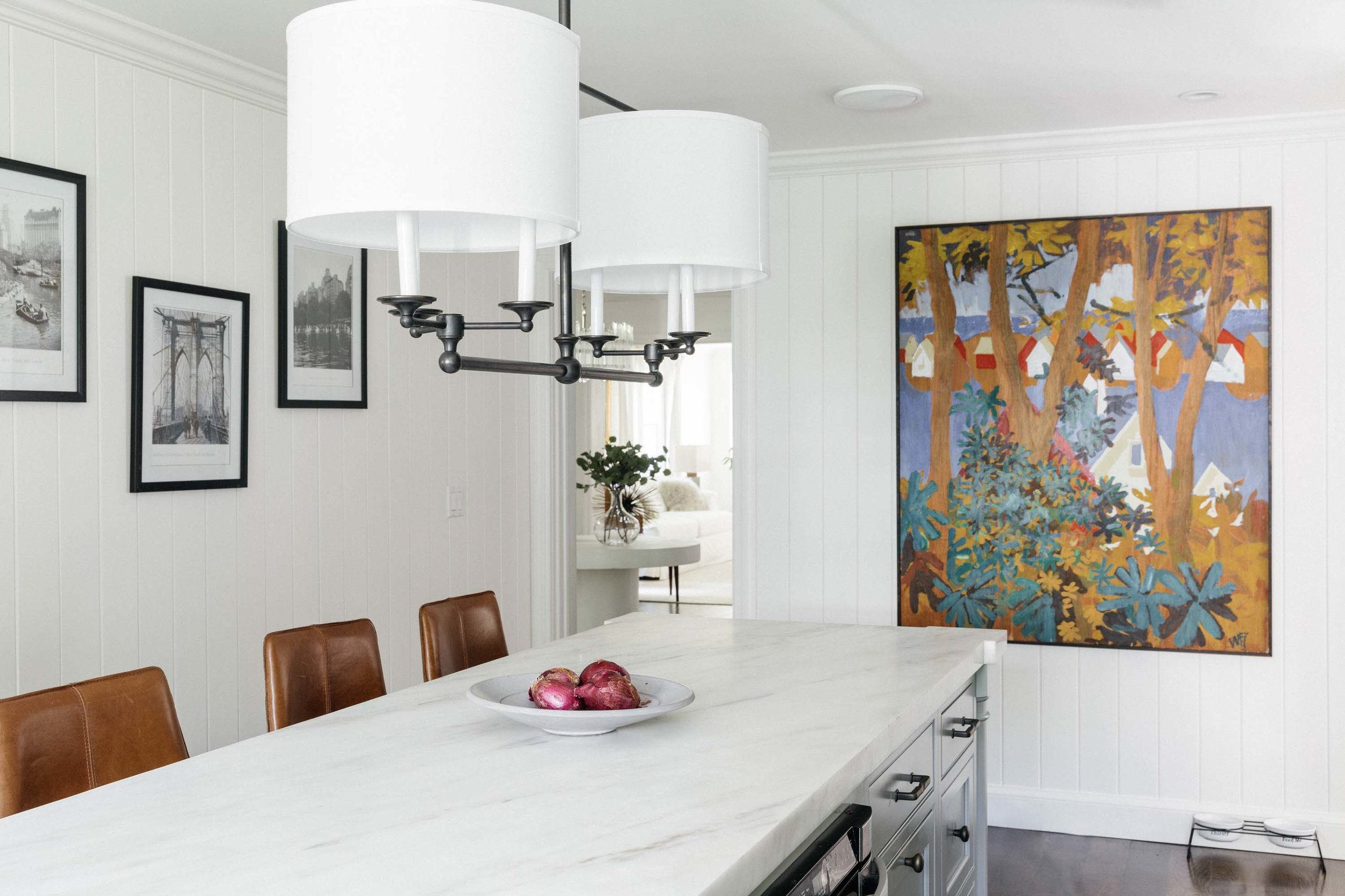 Kitchen with ceramic center island, frames and artwork on the wall