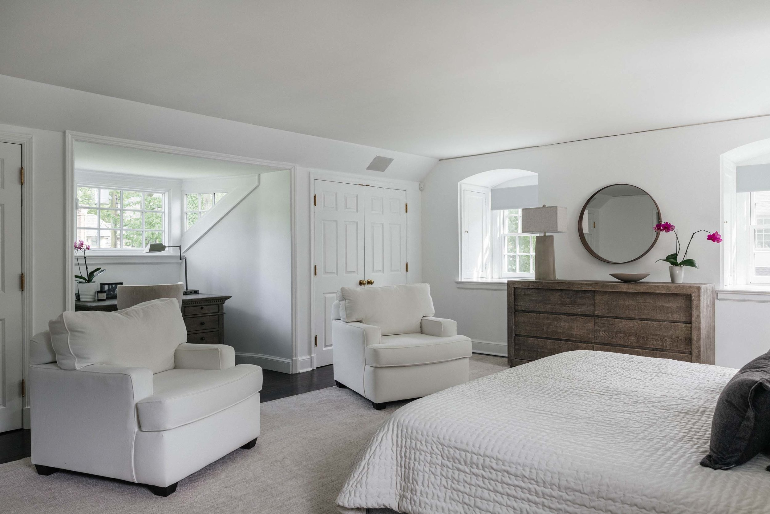 Bedroom with white painted wall, white arm chairs and white door