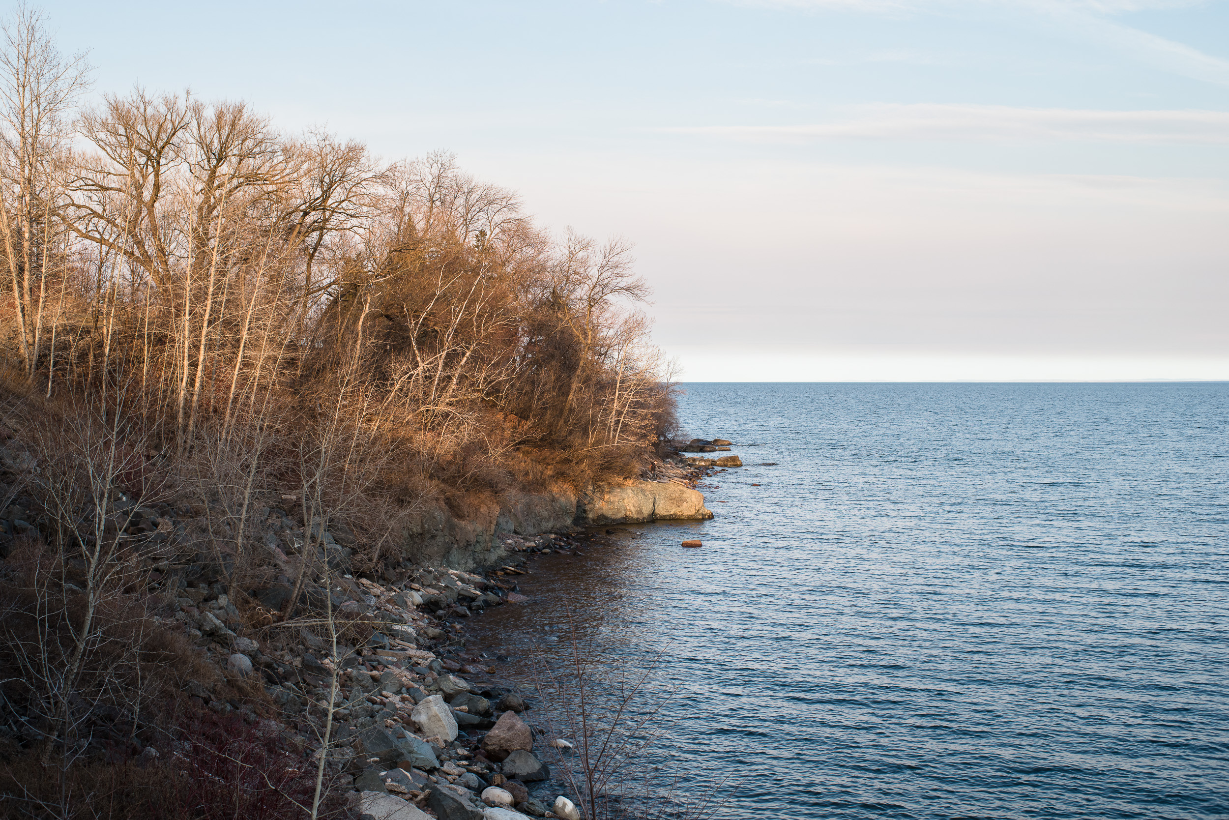 A hard to see boy explores the rock ledge. Lake Superior, Duluth, MN. #lakesuperior #shore #blue #water #43mm #spring