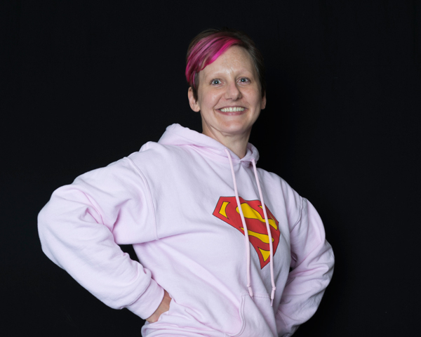 Lindsay McNally posing in her Super Girl hoodie for The Reveal Mission art show, which you can see at the Boise State Student Union Building through Oct. 31.