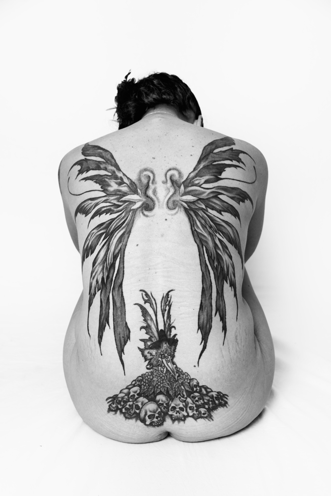 A tattooed fairy sits atop of a pile of skulls on Skyla's lower back. Wings that she designed decorate the rest of her back and shoulders, representing the ability to rise above the destruction she has faced in her life.