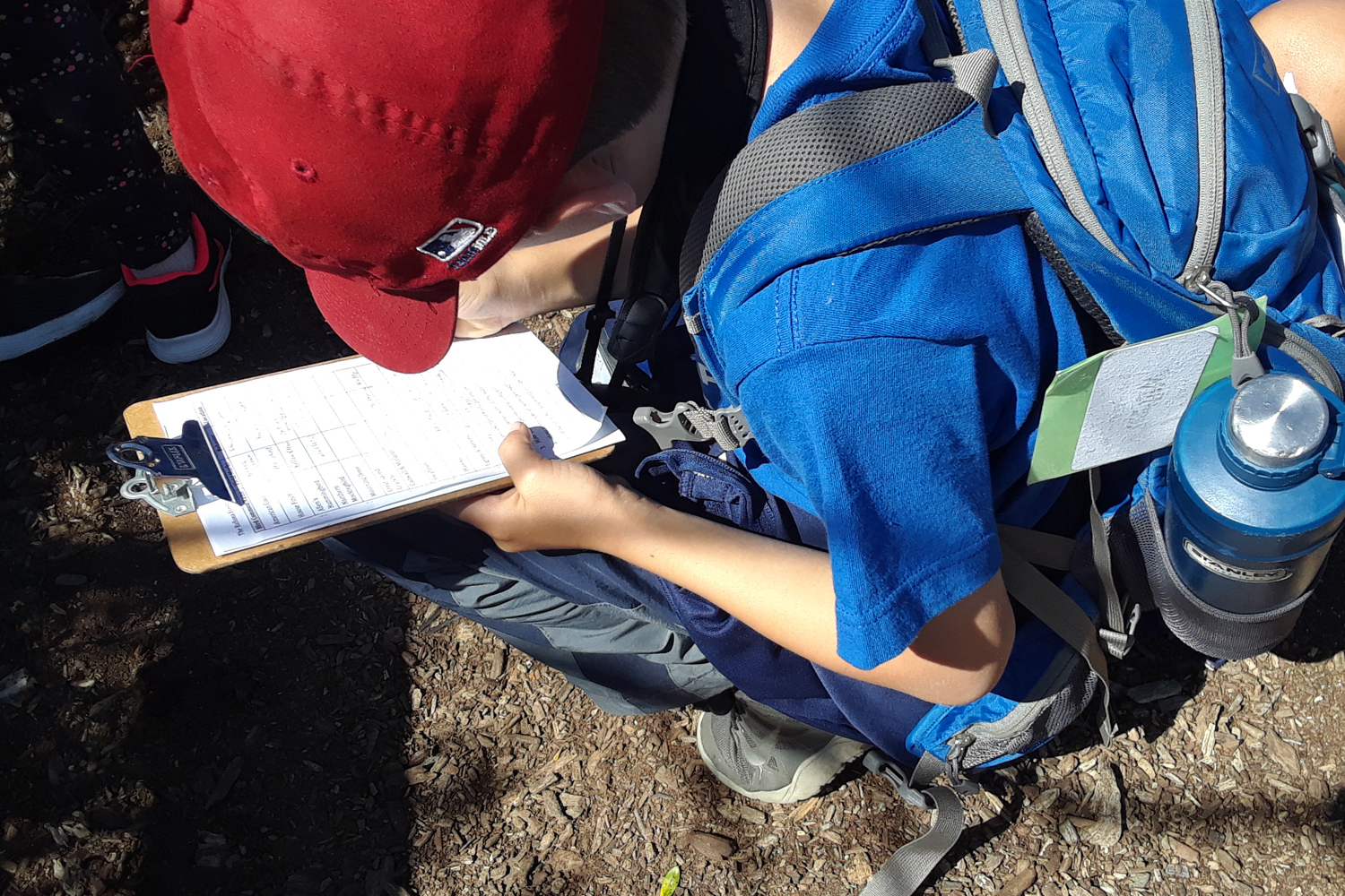 Close-up of camper taking notes