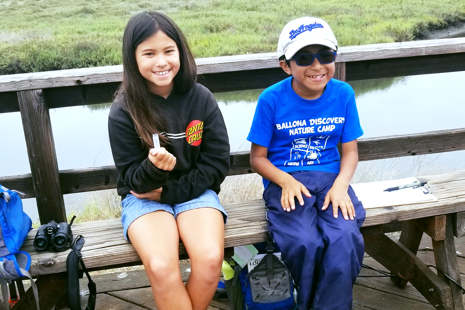 Two campers sitting on trestle at Saltwater Marsh