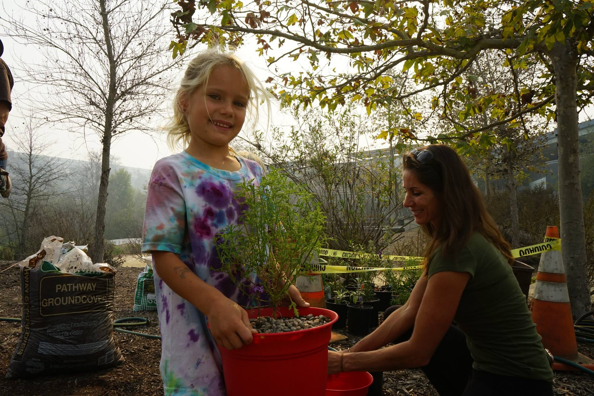 Young girl holding a potted plat at Grow Native Event