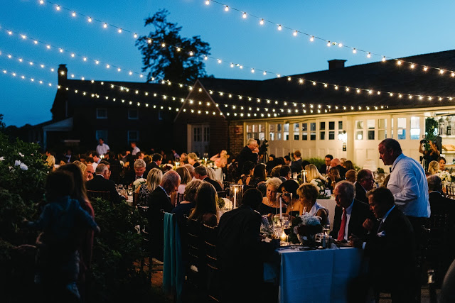 """""""The Froggy's-catered dinner was served outside in the courtyard lit by flickering candles and strung bistro lights. Like a fireworks display, the full harvest moon rising over the traditional boxwood gardens drew a crowd on the east side of the barn after we finished dining.""""- Lindsay + Rob, Chicago Style Weddings Magazine -"""