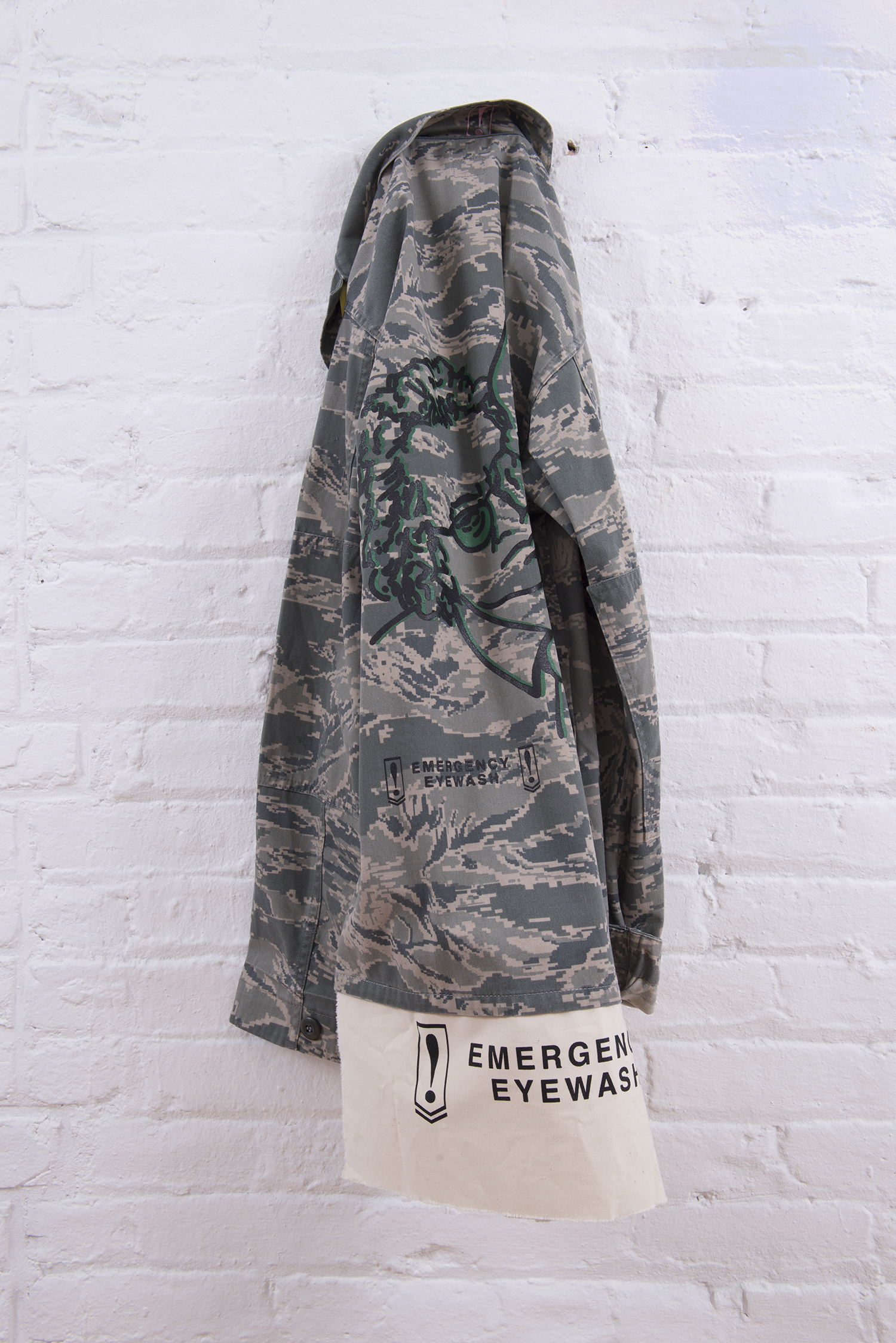 Ahem. Carol Szymanski & Xiaofu Wang. 2018. Vintage military camouflage jacket with Emergency Eyewash patches and silkscreen images