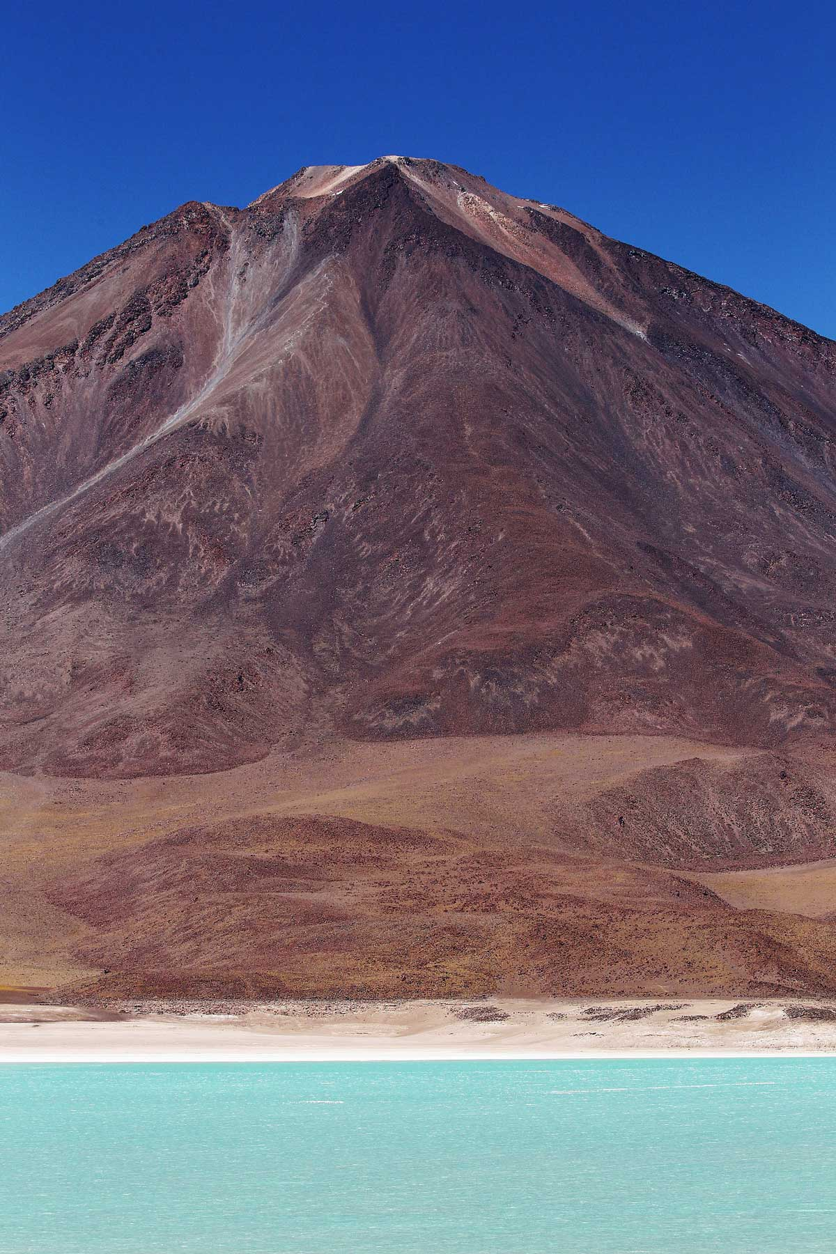 The other-worldly landscape of Bolivia's Altiplano is ringed in vast, desolate plains stained ochre and rust-brown, and speckled with turquoise lagoons that turn a brilliant emerald green when the wind blows