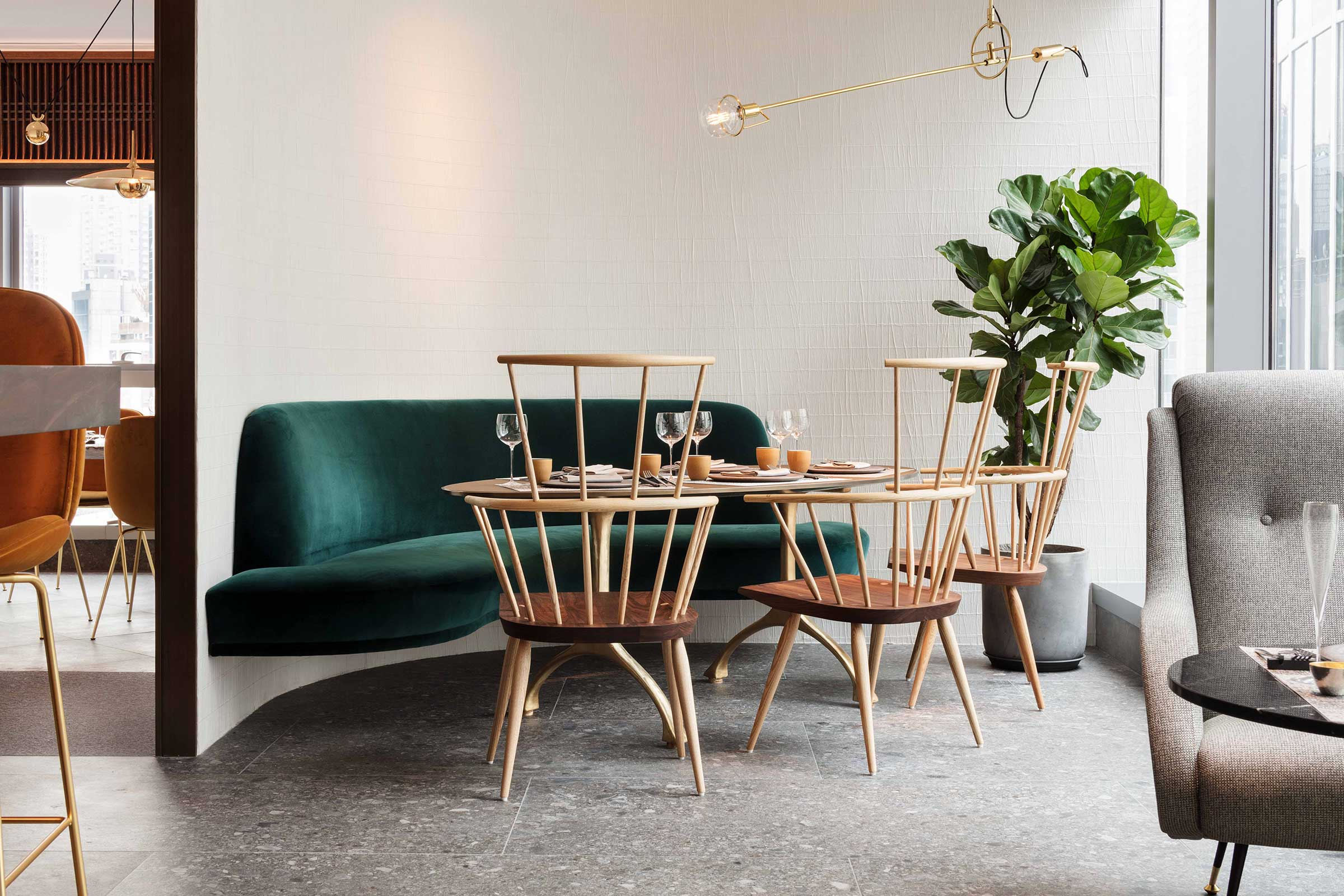 A ceiling pendant by Jader Almeida from  Sollos  is suspended over the banquette with modern windsor chairs by Matthew Hilton from  De La Espada