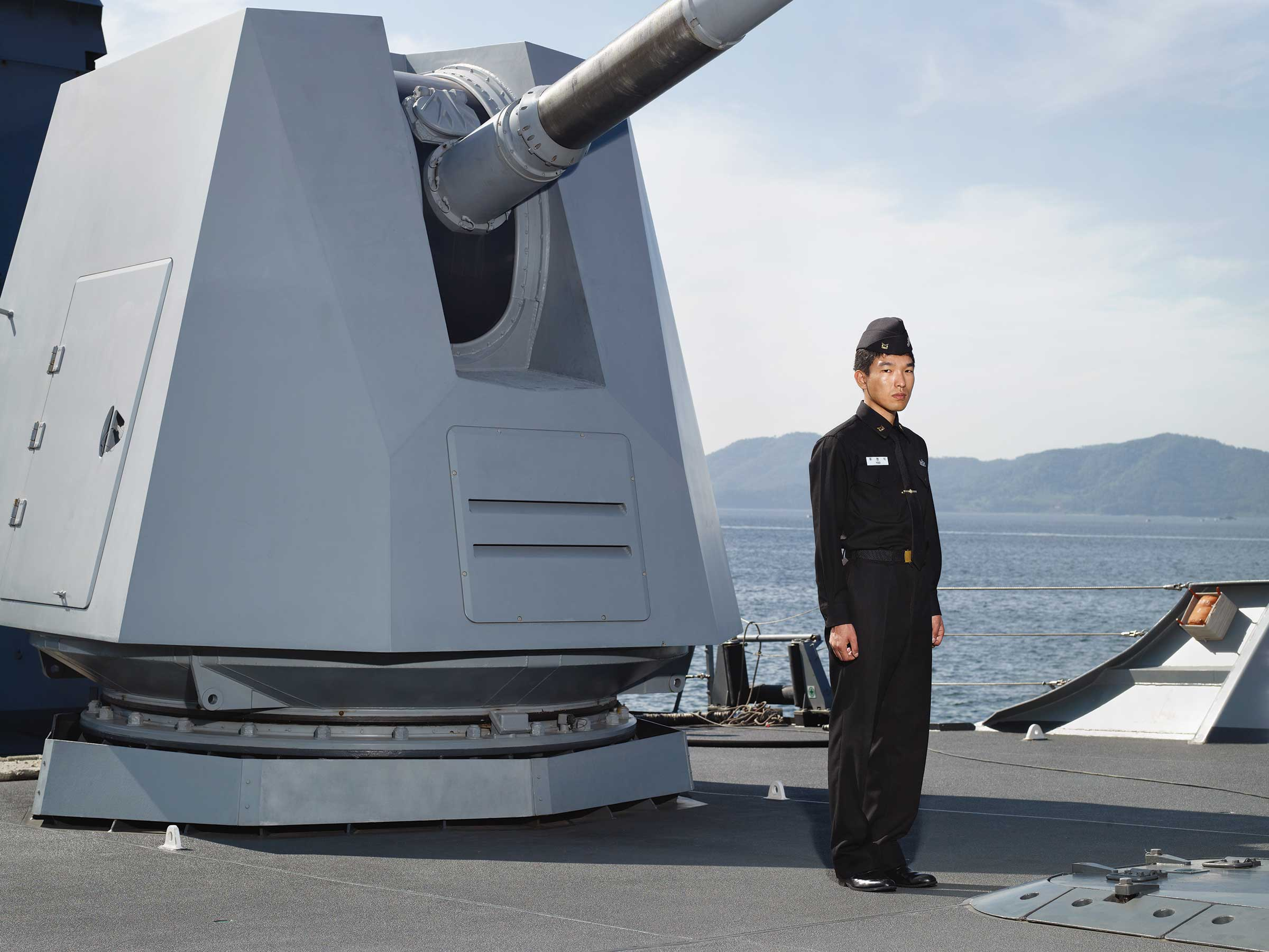 Heinkuhn OH,  A petty officer standing in front of 127mm naval artillery gun, October 2010 , 2010. 151 x 191cm, C Print. Image courtesy of the artist
