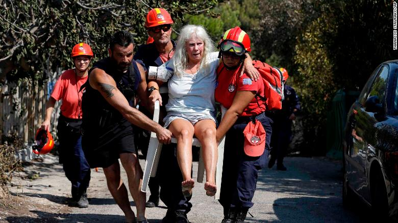 Members of a rescue team carry an injured woman in Mati Wednesday.