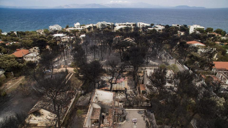 An aerial view shows burnt houses following a wildfire in the village of Mati, near Athens, .(AFP Photo)
