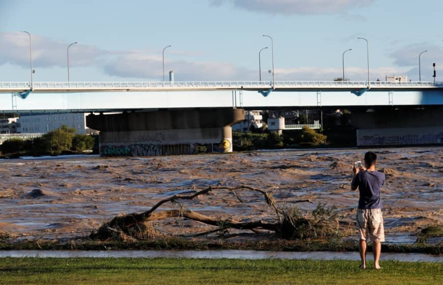 A man takes a picture of the Tama river, which reached flood risk level Saturday night. | REUTERS
