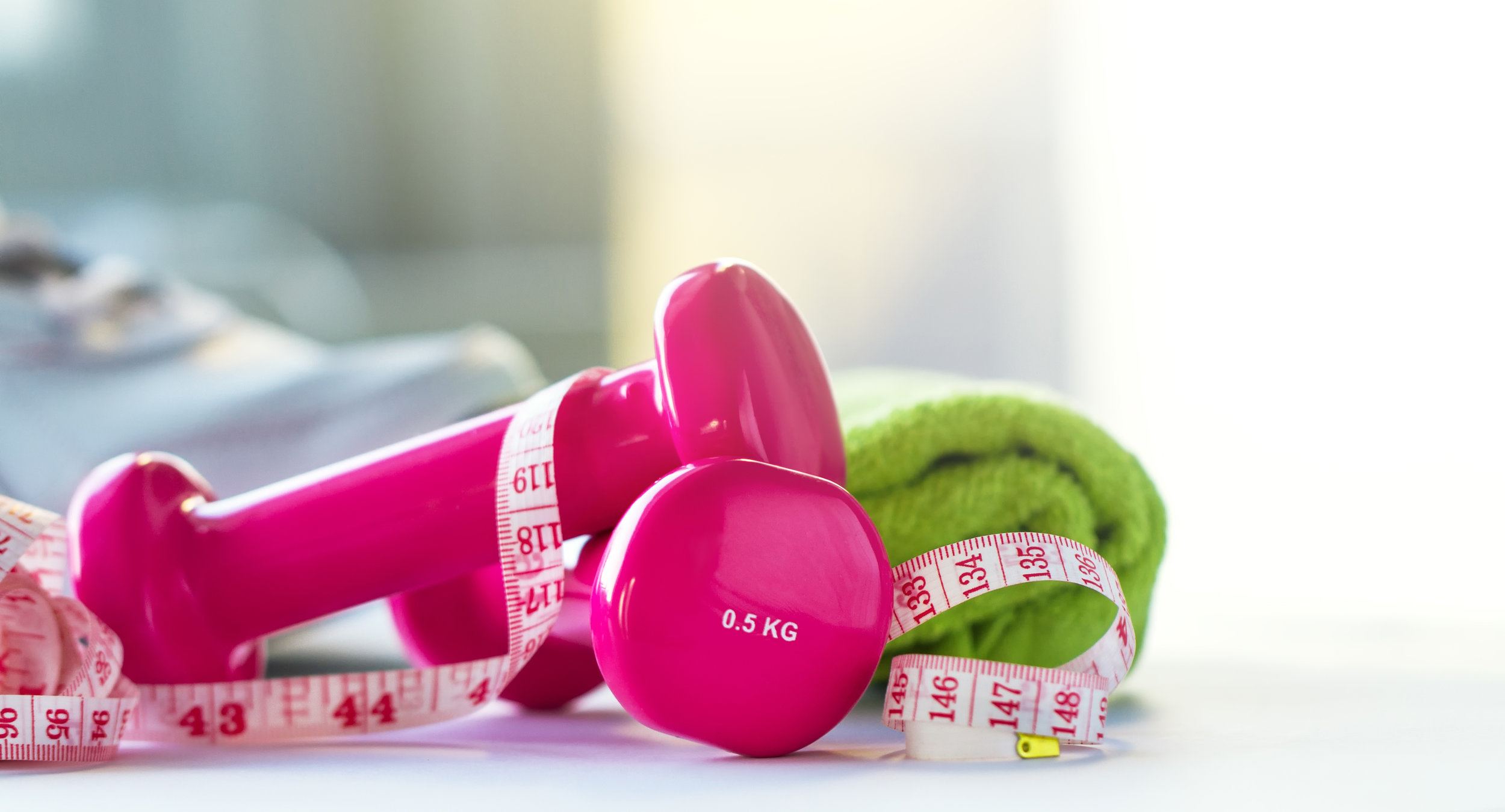 Pair of pink fitness dumbbells with centimeter ribbon on bright