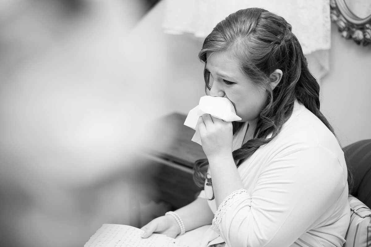 Bride crying while reading love letter from the groom.