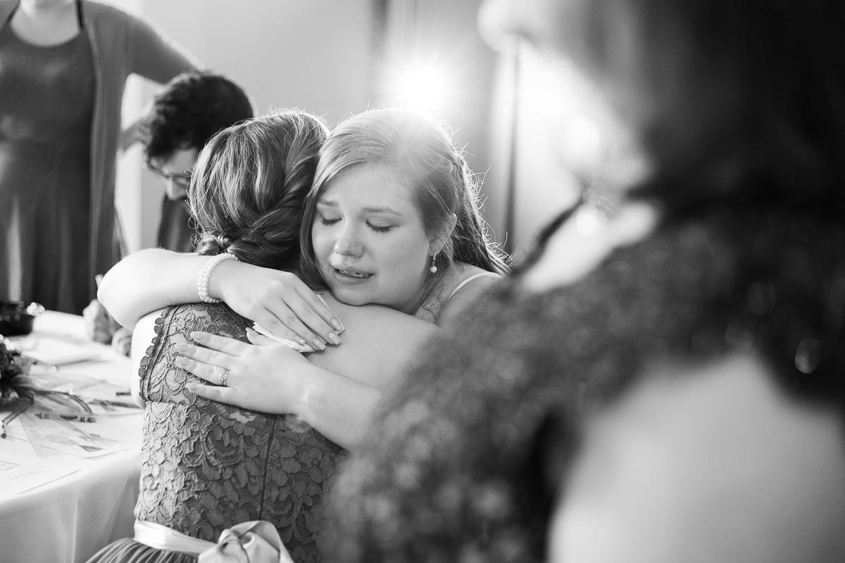 Bride and bridesmaid crying at wedding reception
