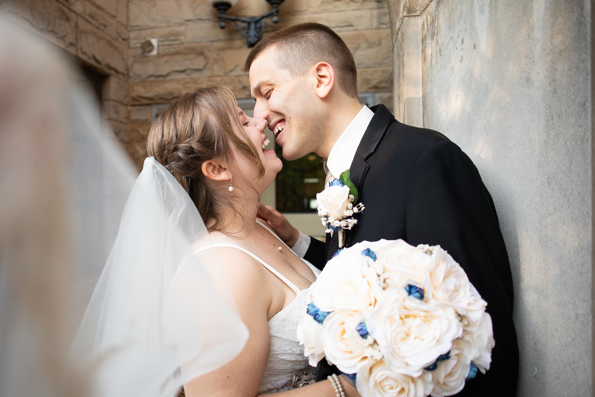 Bride and groom laughing during formal photos.
