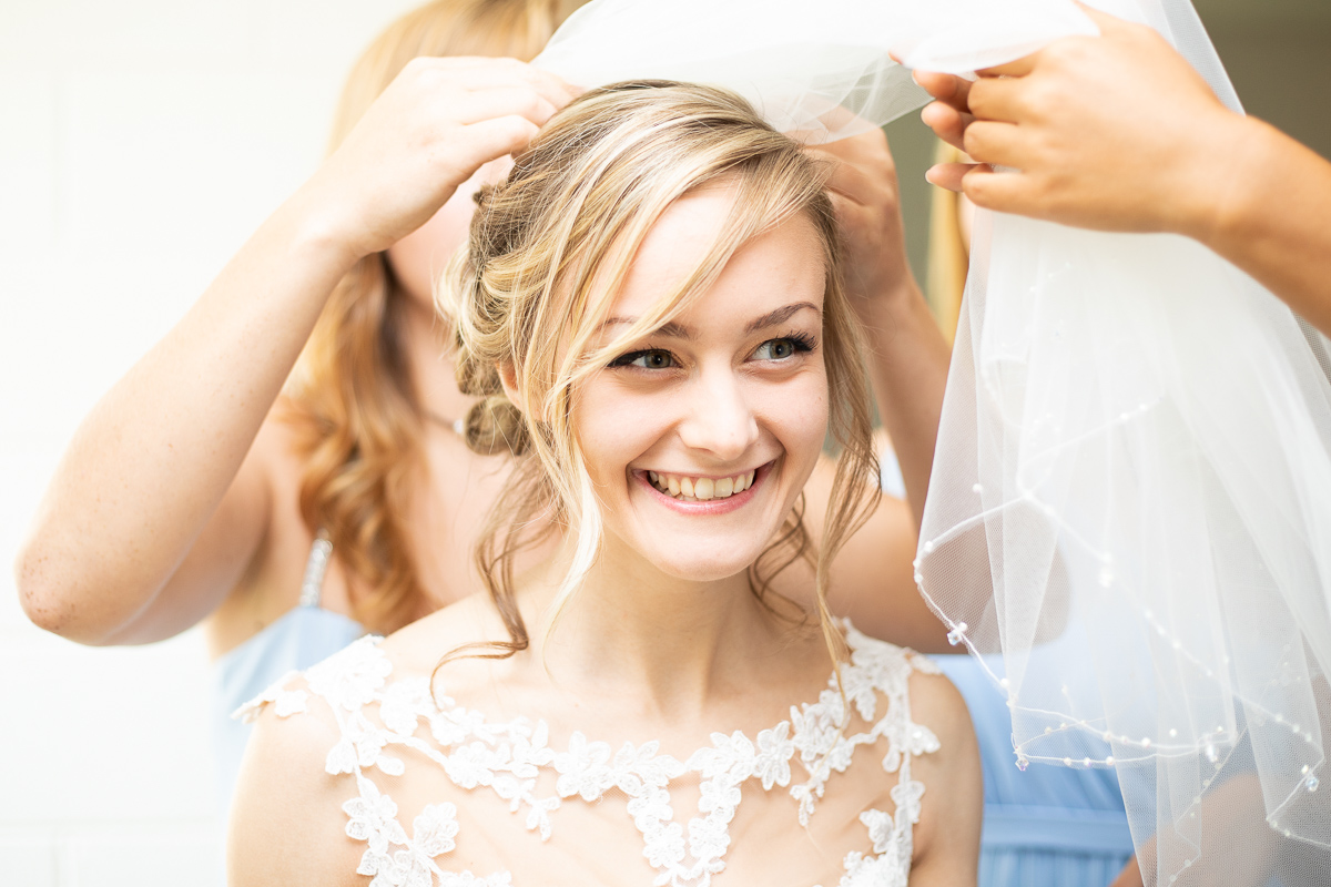 Bride getting ready and putting veil on.