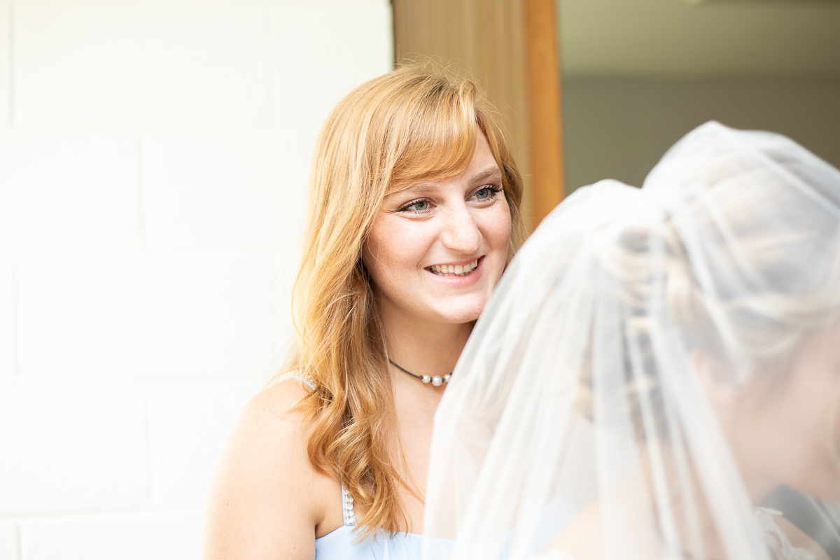 Bridesmaid helping bride put on veil.