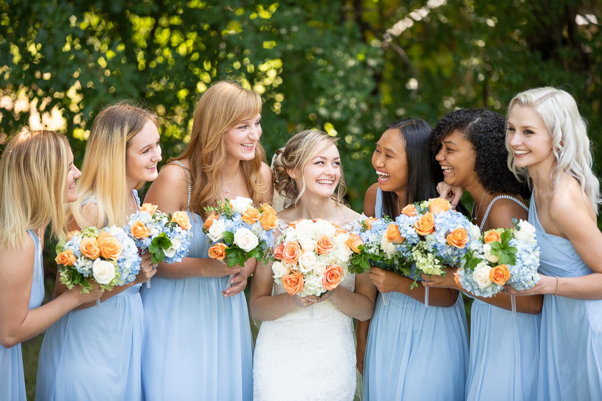Bride and bridesmaids laughing during formal photos.