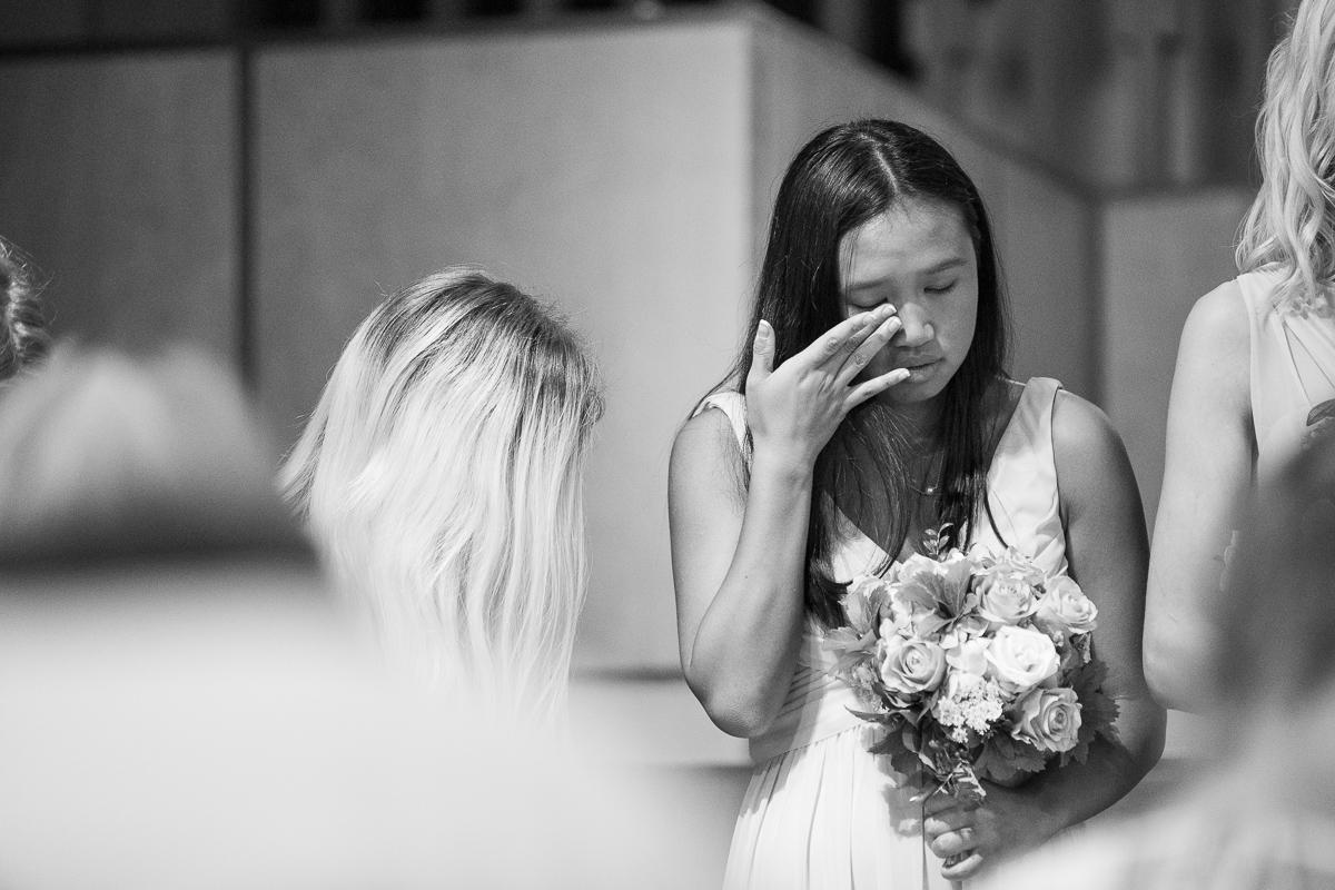 Bridesmaid crying during wedding ceremony.