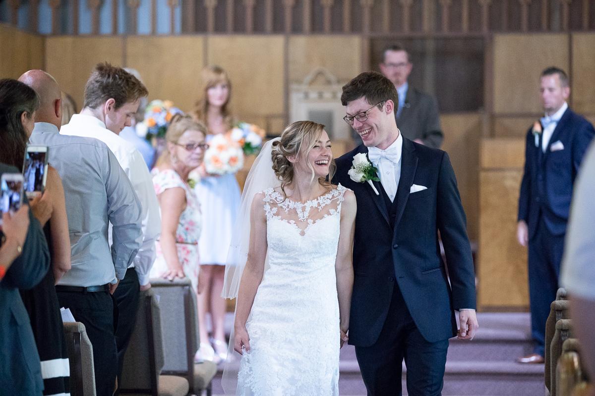 Bride and bridesmaid walking up the aisle smiling.