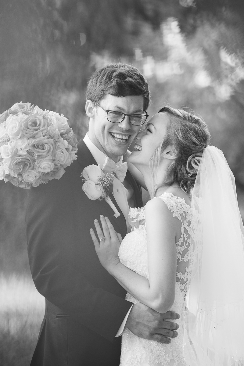 Black and white photo of bride and groom laughing.