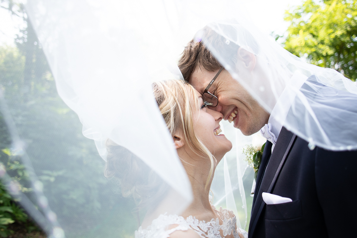 Bride and groom laughing under veil.