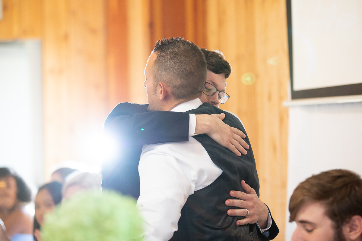 Groom and groomsman hugging during toasts at wedding reception.